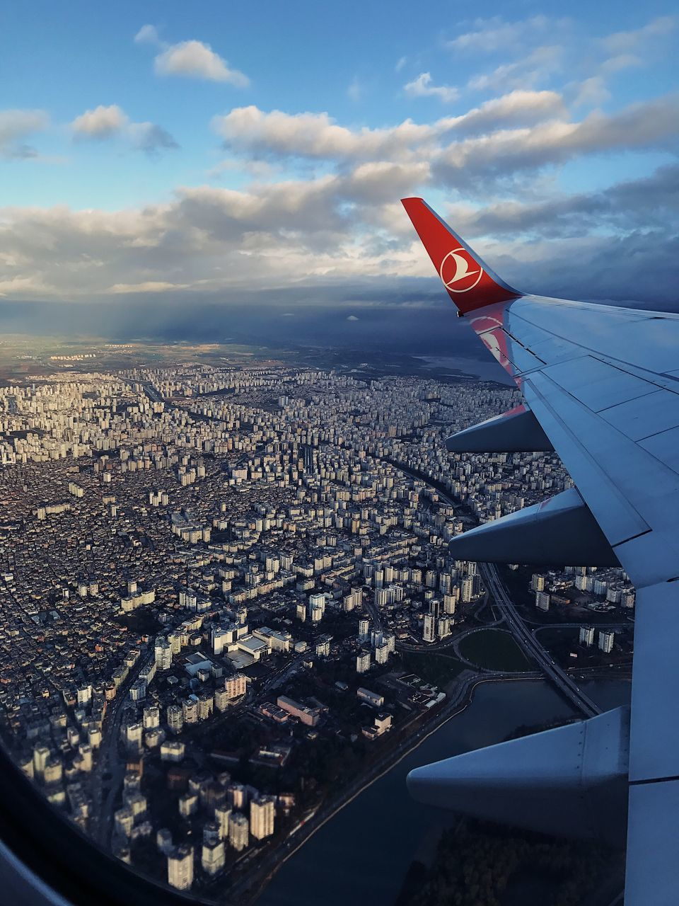 city, cityscape, airplane, architecture, built structure, cloud - sky, aerial view, travel, sky, no people, building exterior, transportation, journey, air vehicle, airplane wing, travel destinations, aircraft wing, outdoors, flying, day