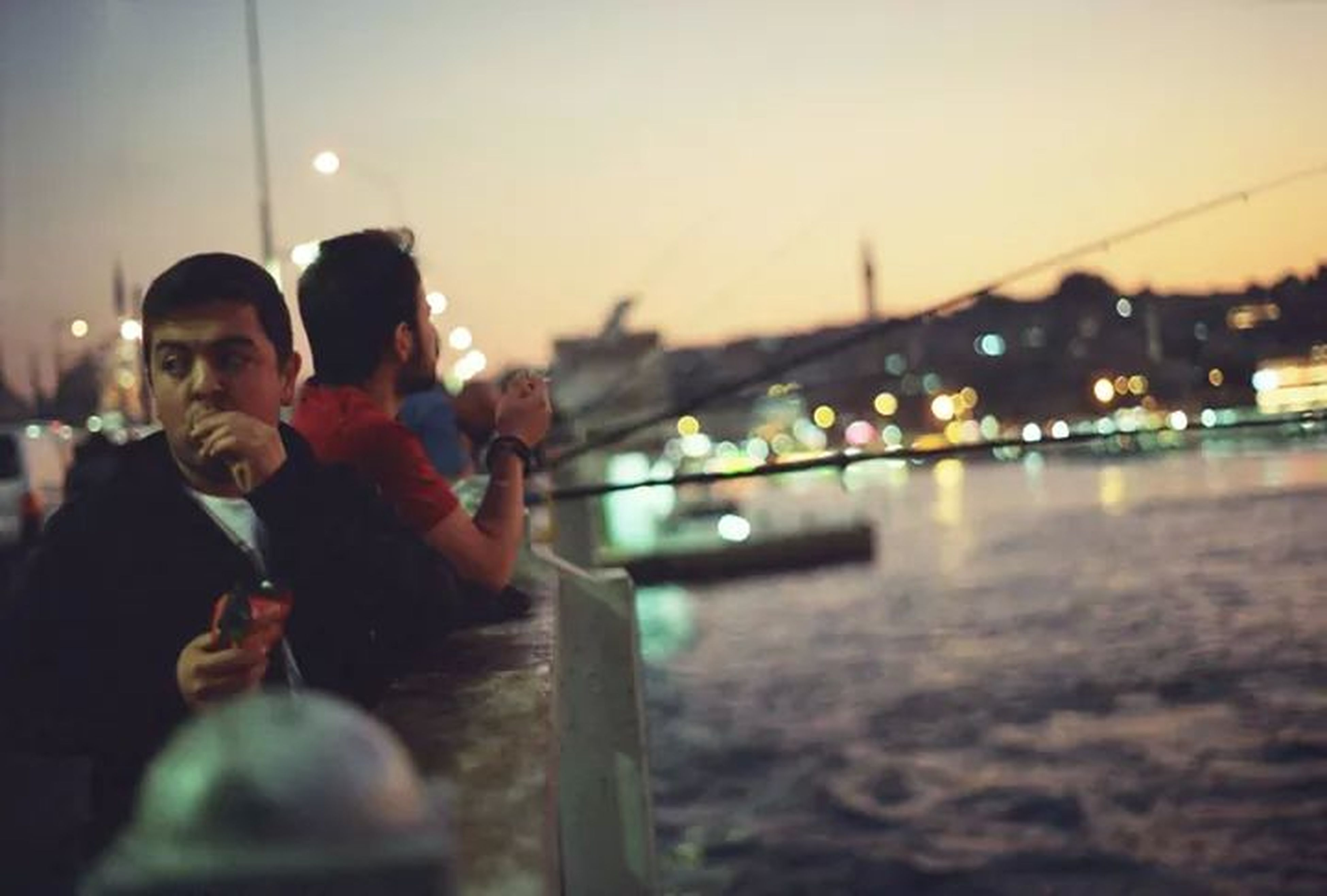 lifestyles, water, leisure activity, men, focus on foreground, person, reflection, clear sky, river, illuminated, outdoors, selective focus, standing, rear view, holding, sky, enjoyment