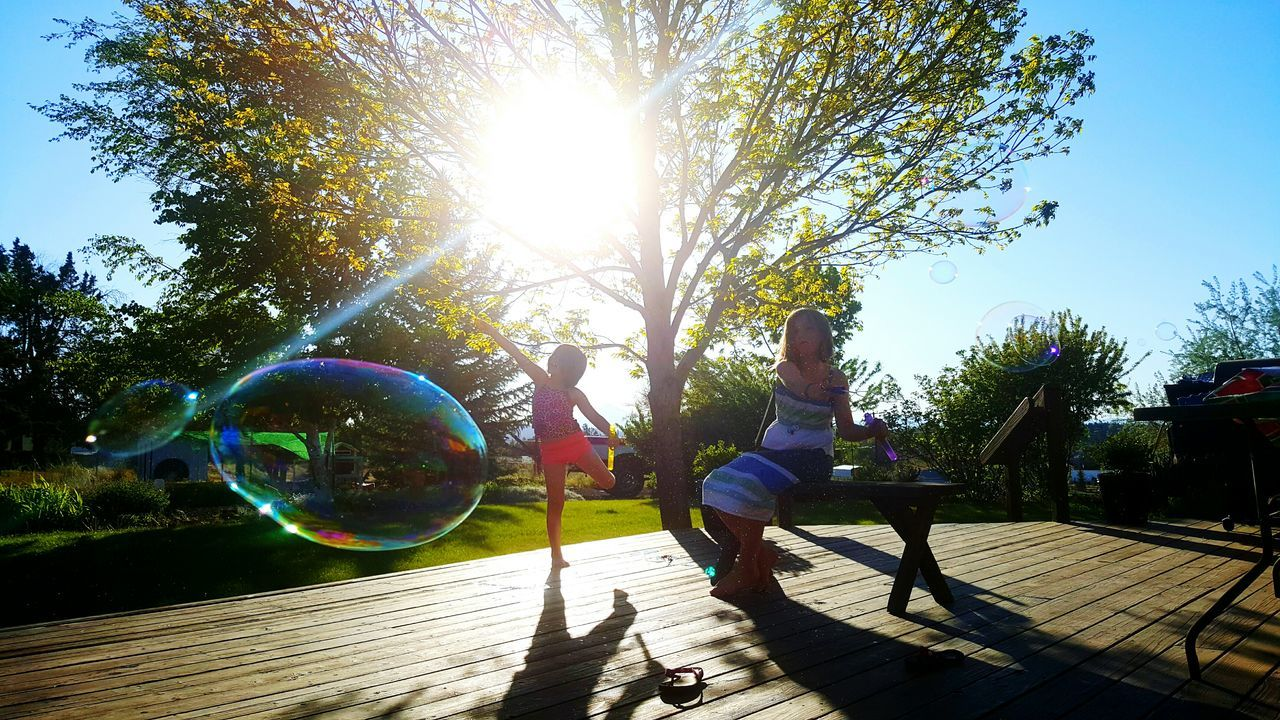sunlight, lens flare, full length, tree, bubble, one person, bubble wand, leisure activity, day, real people, outdoors, lifestyles, nature, childhood, fragility, people, adult