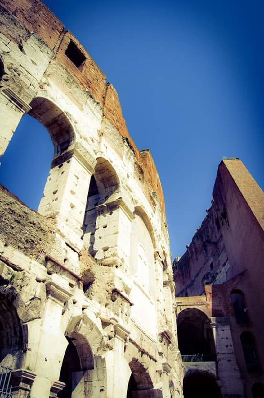 architecture, history, building exterior, built structure, arch, old ruin, low angle view, travel destinations, ancient, day, blue, clear sky, outdoors, sky, no people, ancient civilization
