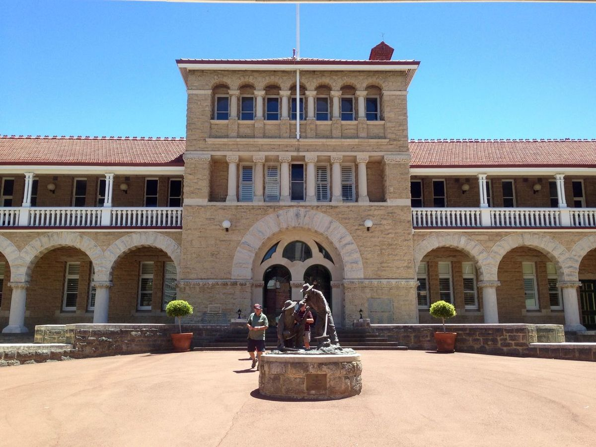 Exterior of the Perth Mint building with tourists in Perth, Western Australia, Australia. Arch Architectural Column Architecture Australia Balcony Blue Building Building Exterior Built Structure Bullion Mint City City Life Courtyard  Day Exterior Façade Incidental People Mint Outdoors Perth Perth Mint Sky Tourists Travel Destinations Western Australia