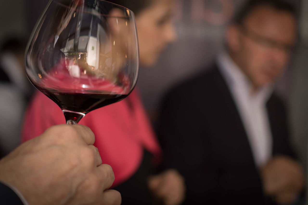 wineglass, wine, real people, men, alcohol, one person, holding, focus on foreground, food and drink, red wine, human hand, human body part, lifestyles, close-up, women, drink, indoors, day, winetasting, adult, people