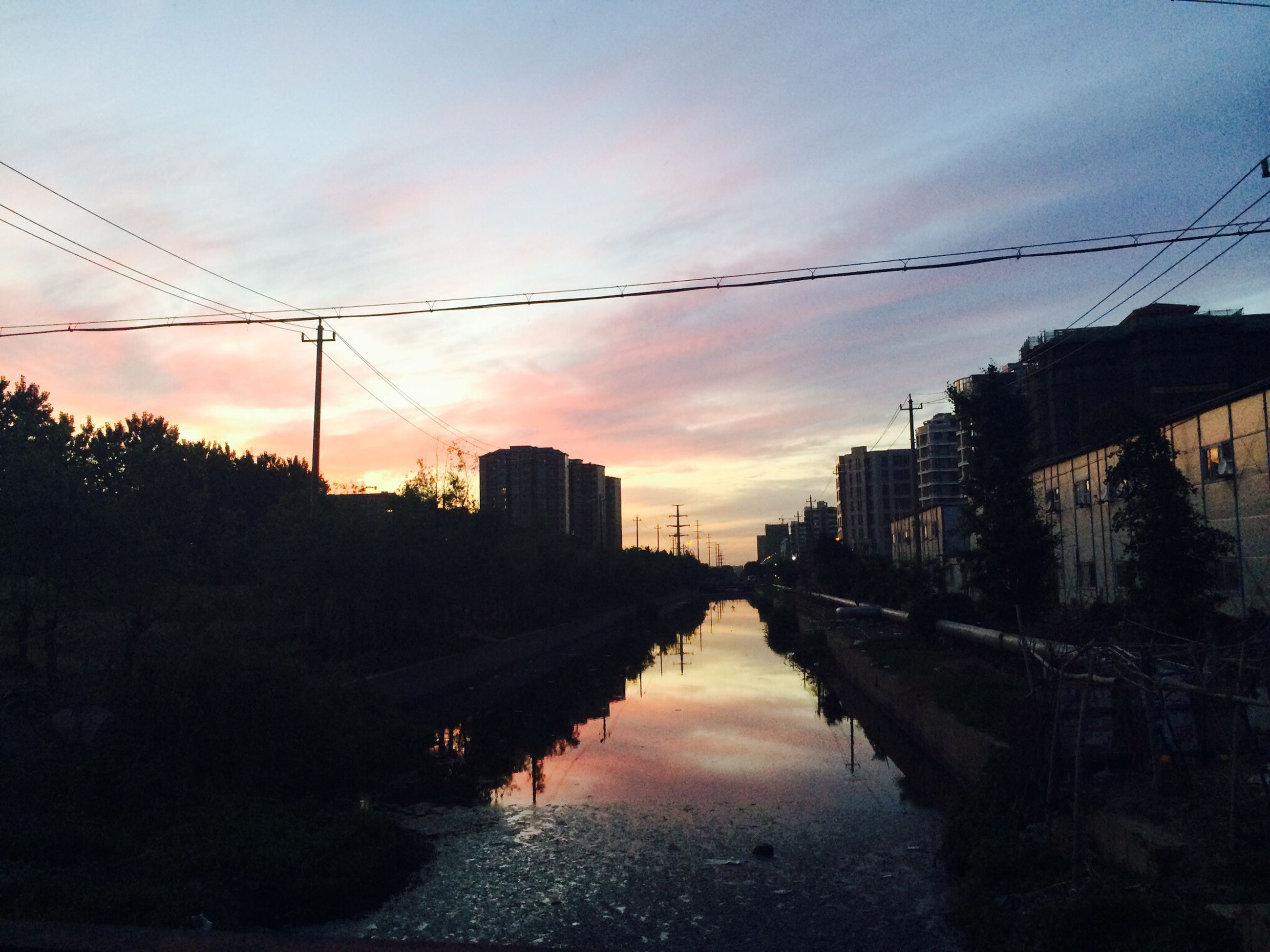 building exterior, architecture, built structure, sunset, power line, water, reflection, sky, electricity pylon, canal, waterfront, cable, connection, river, cloud - sky, silhouette, city, residential structure, electricity, house