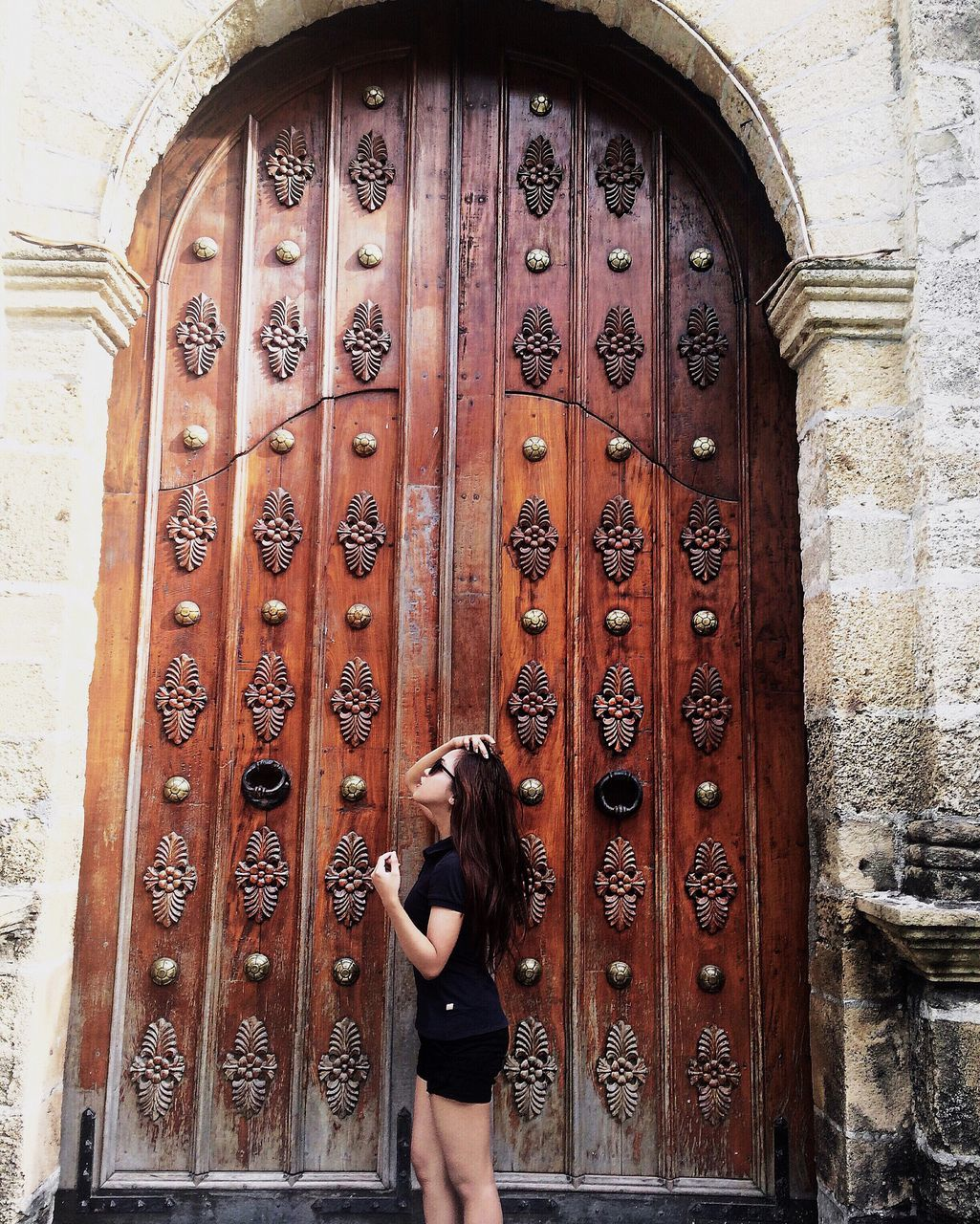 door, real people, one person, lifestyles, day, leisure activity, outdoors, beautiful woman, standing, architecture, young women, young adult, people
