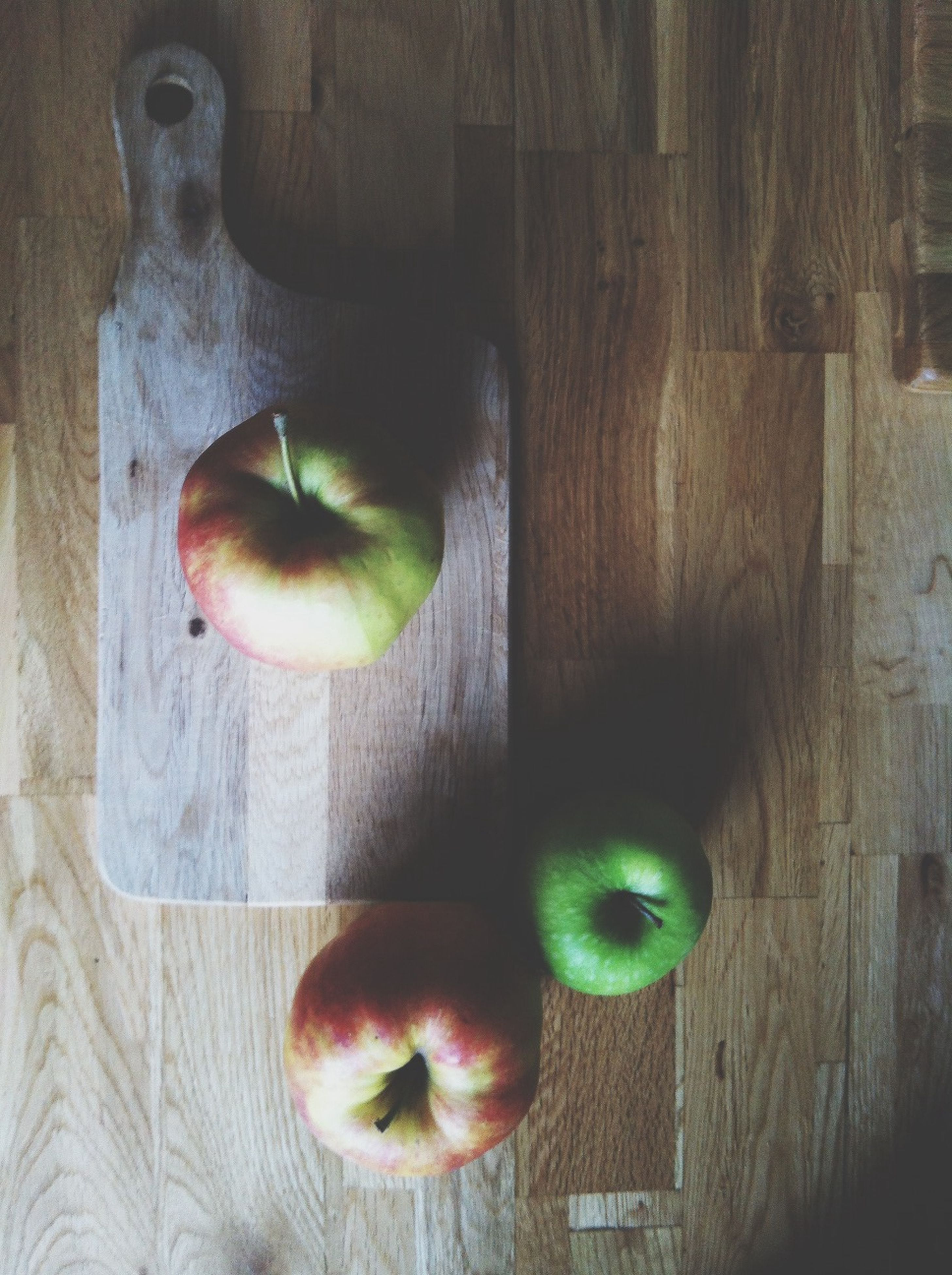 indoors, table, food and drink, wood - material, food, healthy eating, fruit, still life, green color, close-up, wooden, high angle view, freshness, apple, wood, no people, toy, vegetable, childhood, animal representation