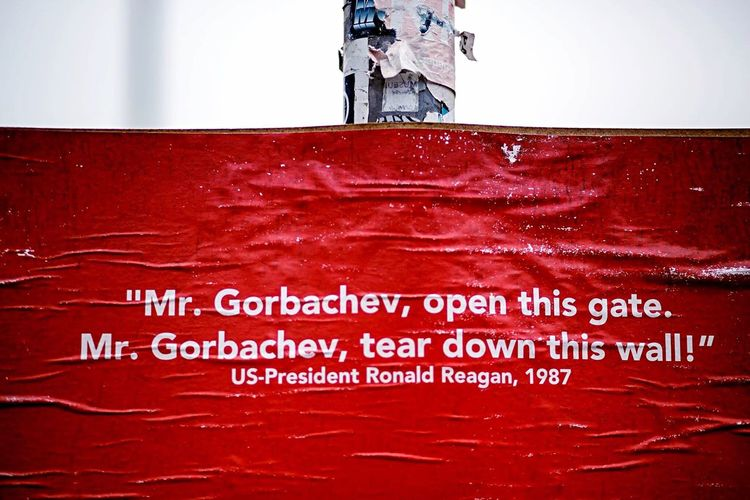 Text Red No People Poster Textured  Berlin Berlin Wall Rain Landpost Depth Of Field Ronald Reagan  Cold War Political Statement White On Red Warped  Wrinkled Paper Day