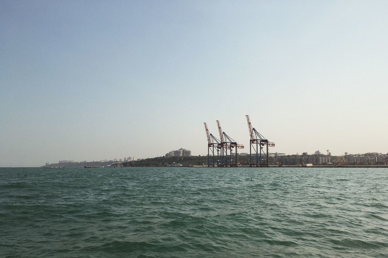 waterfront, clear sky, sea, water, copy space, crane - construction machinery, outdoors, no people, day, built structure, sky, nature, architecture, commercial dock, transportation, shipping, freight transportation, beauty in nature, scenics, industry, nautical vessel, building exterior