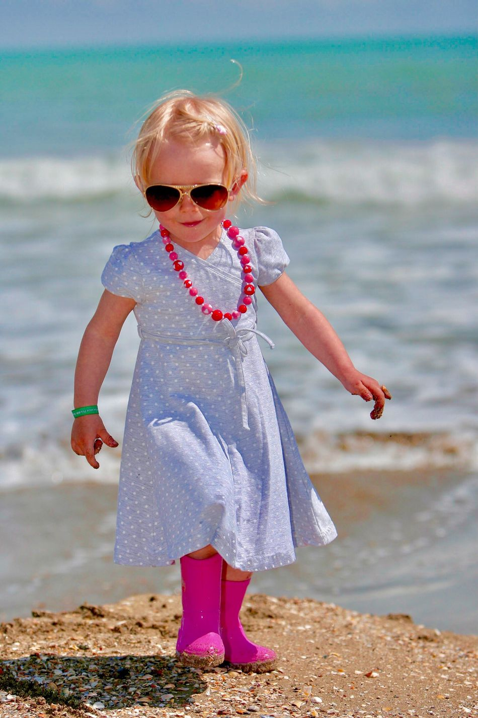 Little Polish girl of typical Slavic fashion dressed up and exceptionally dressed for the sea pink roses, pink necklace and sunglasses Sunny escaped mum for this blue dress against the turquoise Italian coast in the area of Venice Sunglasses One Person Real People Childhood Sea Sand Standing Elementary Age Leisure Activity Outdoors Fashion Cute Girl Water Lifestyles Focus On Foreground Front View Little Polish Girl Fashionable Travel Travel Destinations Italy Coastline