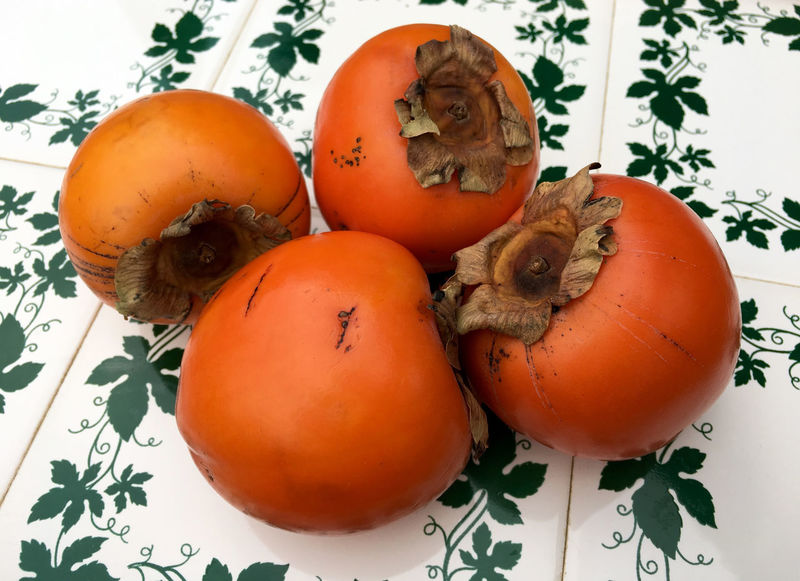 Fresh persimmons in closeup Close-up Day Detail Food Food And Drink Freshness Fruits Growth Healthy Eating Kaki Kaki Fruit Nature No People Nutrition Orange Color Organic Food Outdoors Persimmon Still Life Vegan Food Vitamin C