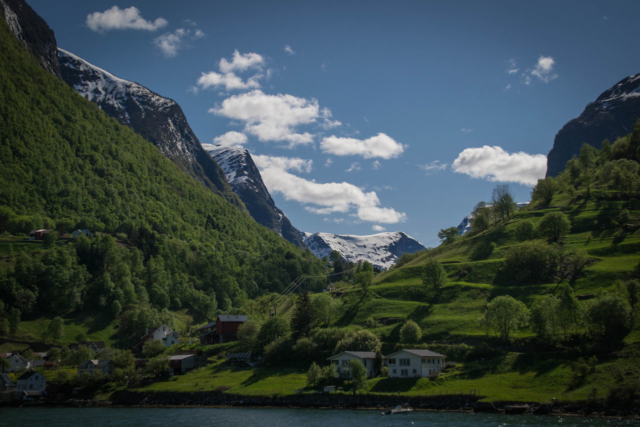 A small village surrounded by a fjord and mountains in western Norway. Norway Undredal Western Norway Beauty In Nature Cloud - Sky Day Fjord Green Color Landscape Mountain Mountain Range Nature Outdoors River Scenics Sky Tranquil Scene Tranquility Tree Water Waterfront