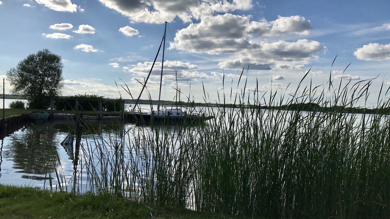 sky, cloud - sky, nature, grass, tranquil scene, water, outdoors, tranquility, day, lake, no people, scenics, beauty in nature, growth, plant, nautical vessel