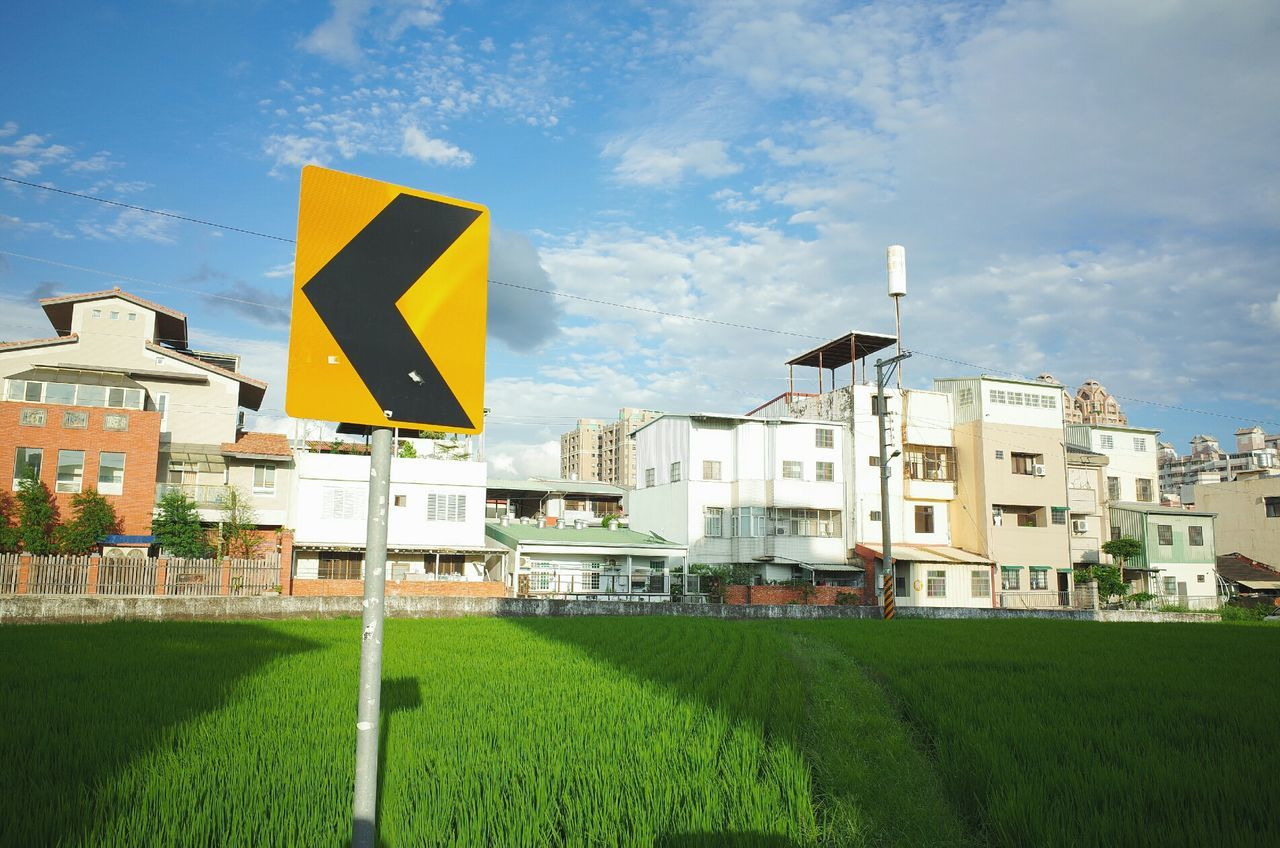 Buildings against sky with roadsign on lawn in foreground