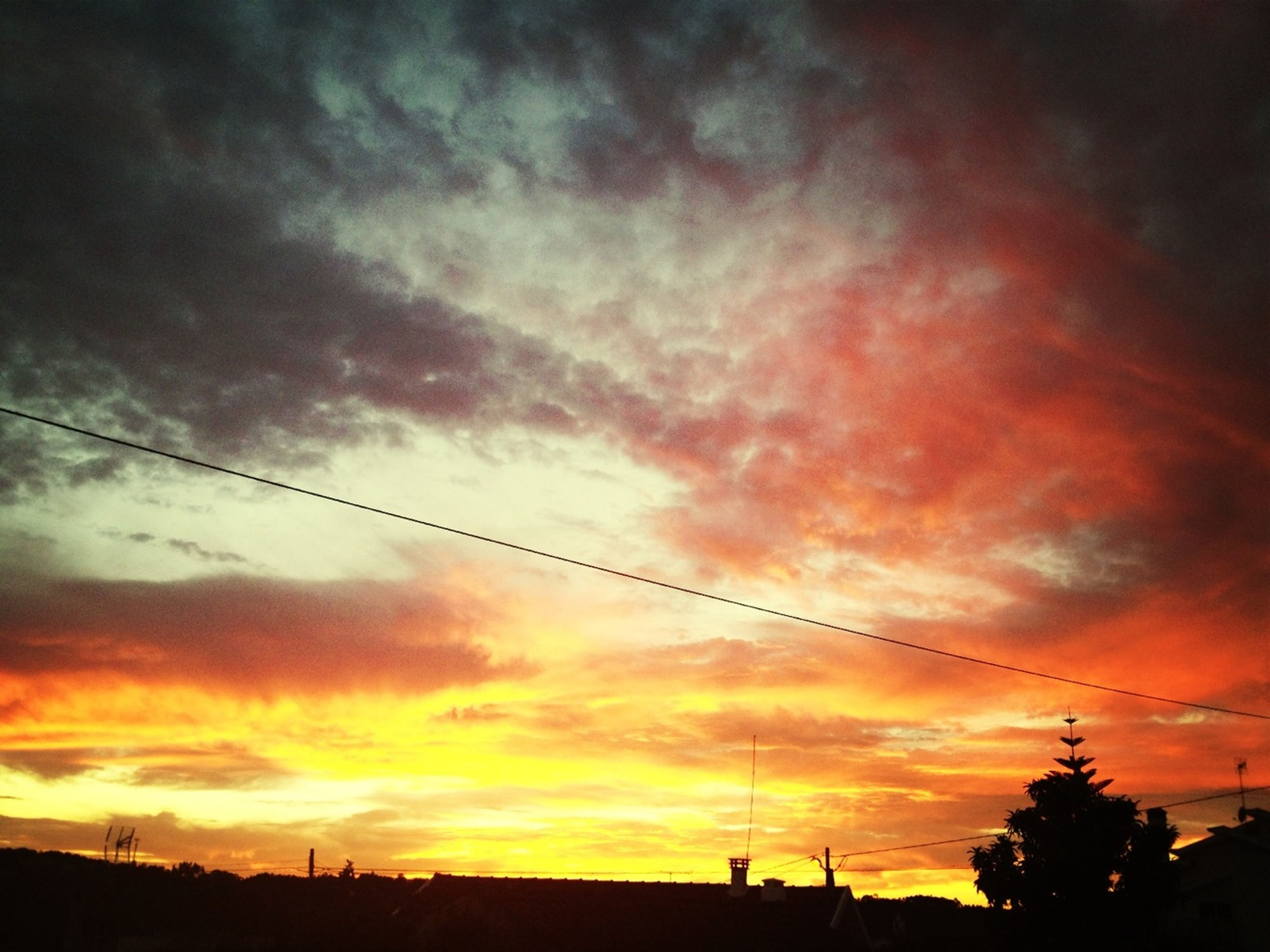 sunset, silhouette, sky, power line, electricity pylon, low angle view, orange color, beauty in nature, tranquility, scenics, cloud - sky, tranquil scene, nature, dramatic sky, power supply, connection, cloud, electricity, cable, dusk
