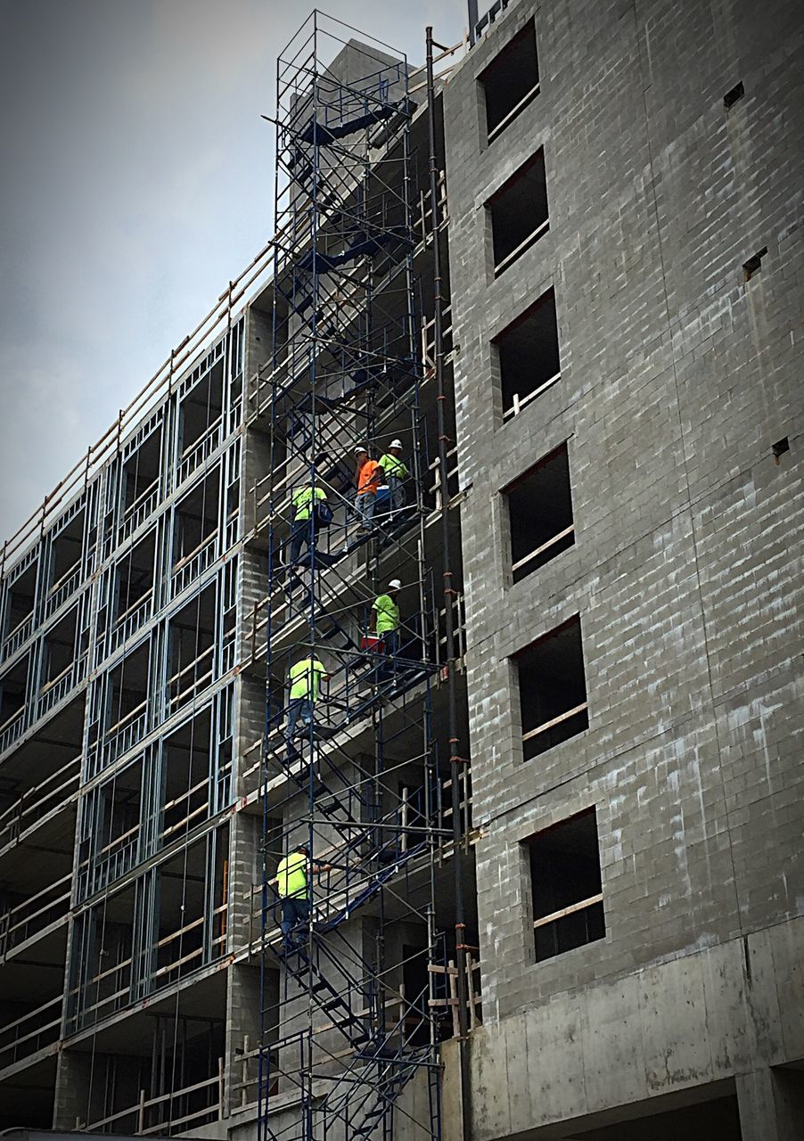 architecture, manual worker, occupation, building exterior, working, window, window washer, built structure, building, men, danger, cleaning, construction site, low angle view, real people, repairing, building - activity, washing, coworker, day, hardhat, outdoors, one person, people, adult