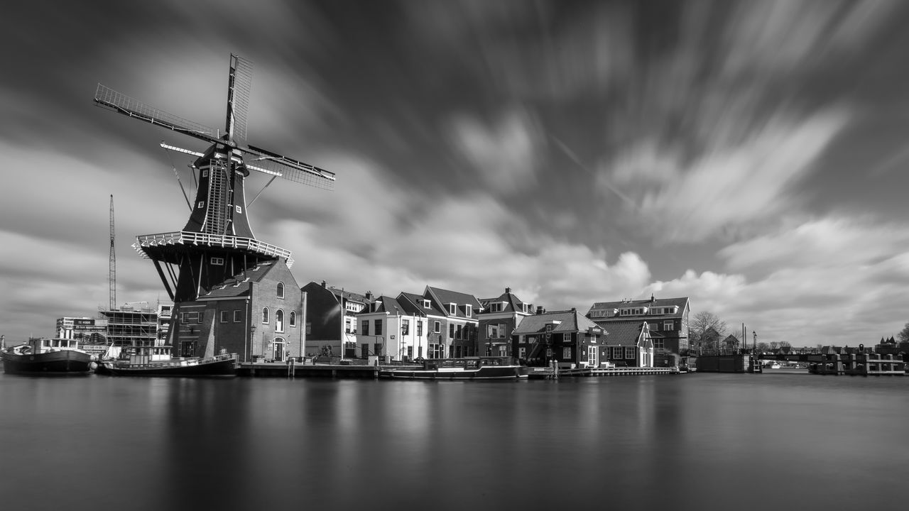 River By Traditional Windmill And Houses Against Sky