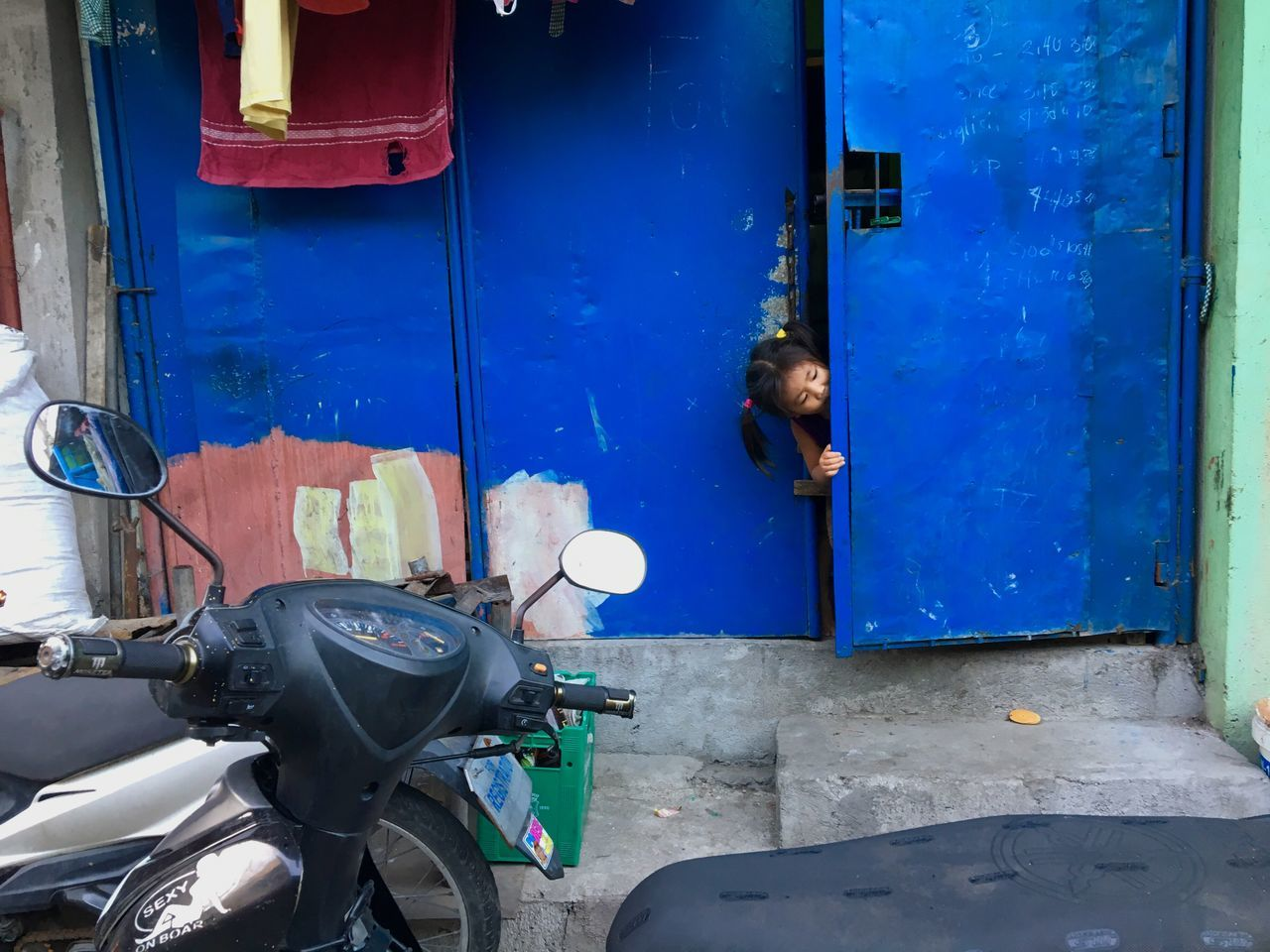 A girl peeks behind an iron gate at Santo Nino neighbourhood in Taguig, Metro Manila. Blue One Person Mode Of Transport Stationary Architecture Built Structure Real People Outdoors Day One Man Only People Little Girl Peekaboo Iron Gate Blue Gate Philippines Taguig Manila Street Photography Peeking Peeking Out