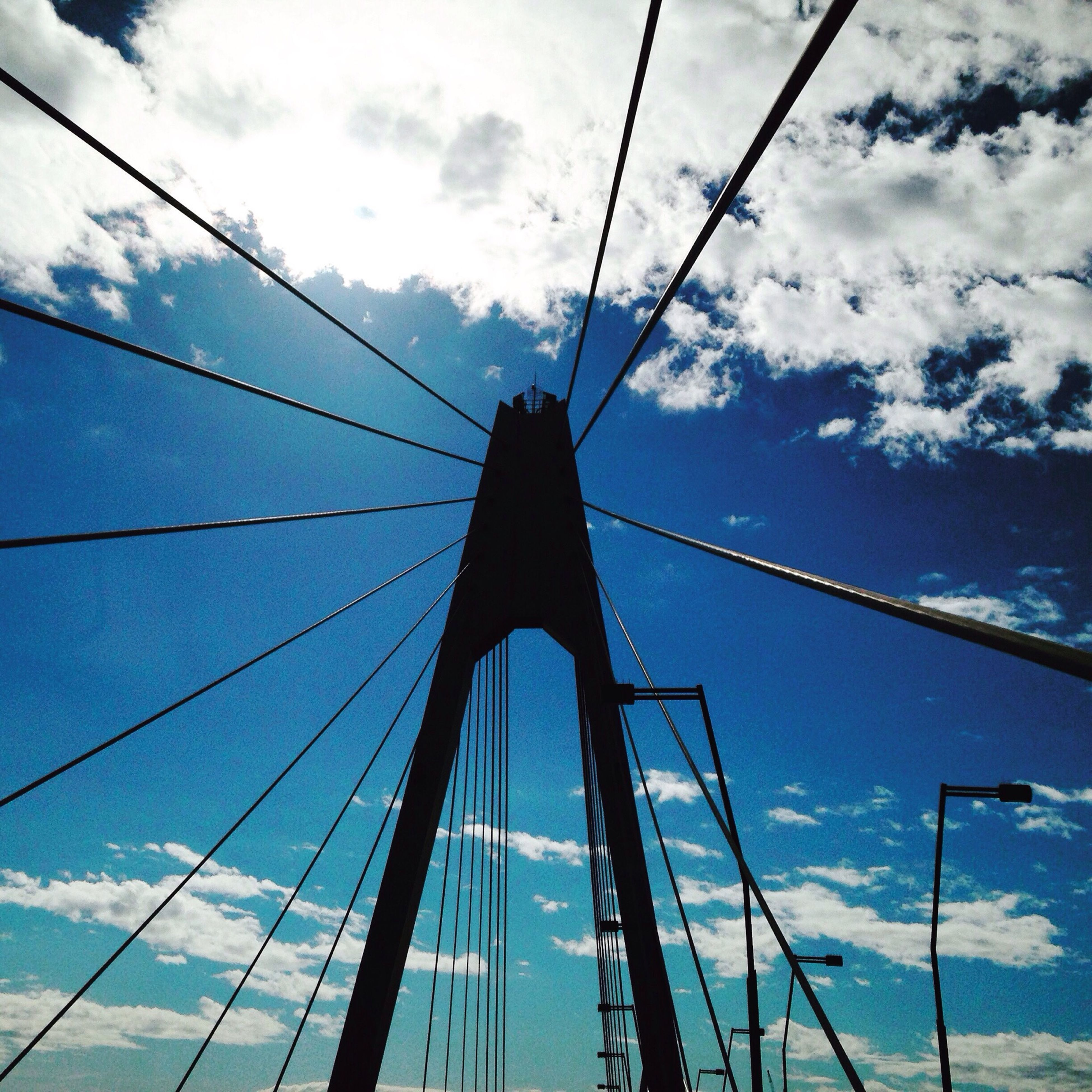 sky, transportation, low angle view, connection, cloud - sky, mast, suspension bridge, nautical vessel, cloud, engineering, cloudy, cable-stayed bridge, bridge - man made structure, blue, steel cable, mode of transport, built structure, cable, part of, sailboat