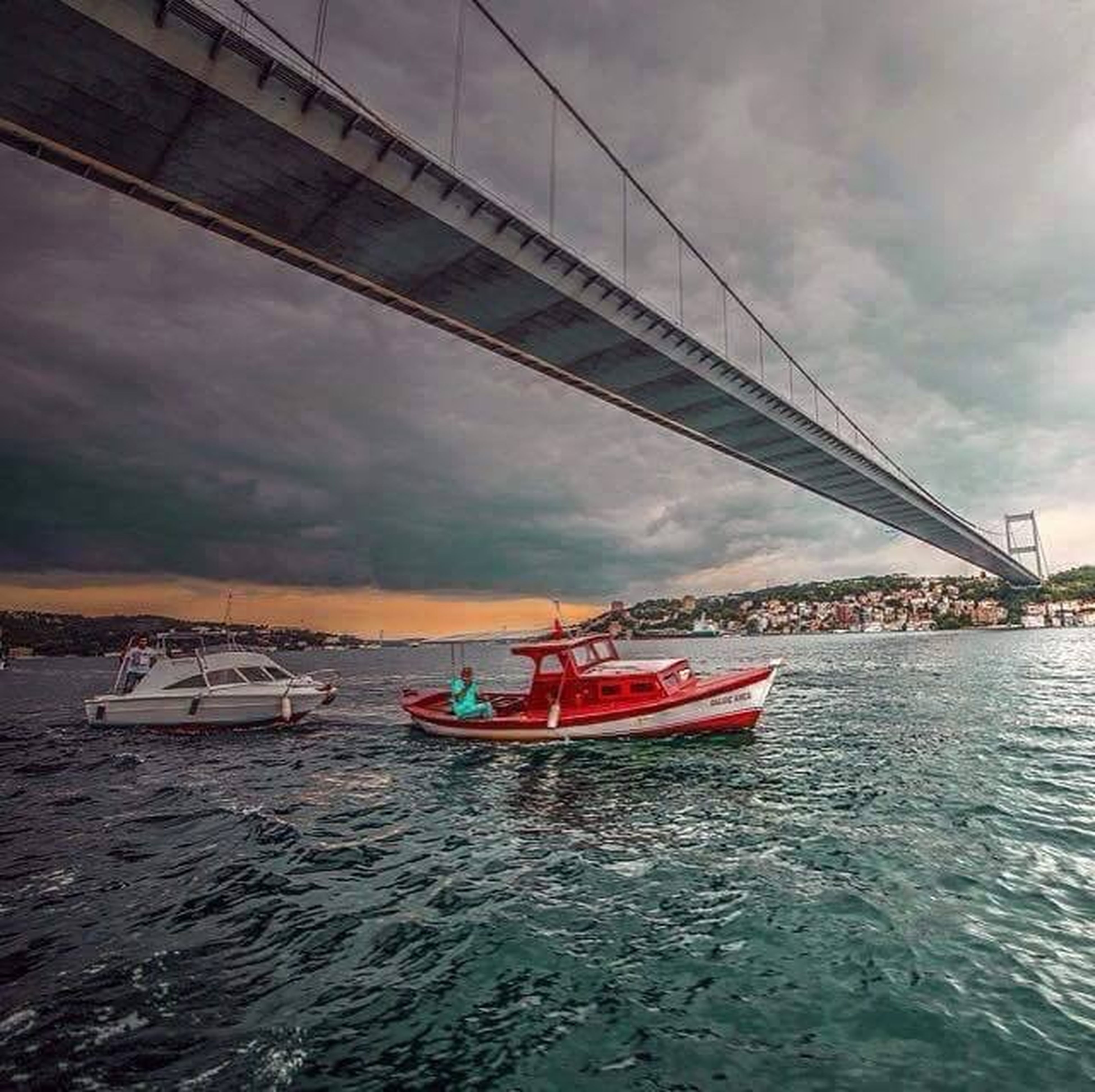 transportation, nautical vessel, water, sky, waterfront, cloud - sky, mode of transport, boat, cloudy, sea, built structure, cloud, architecture, rippled, river, sailing, travel, moored, overcast, bridge - man made structure