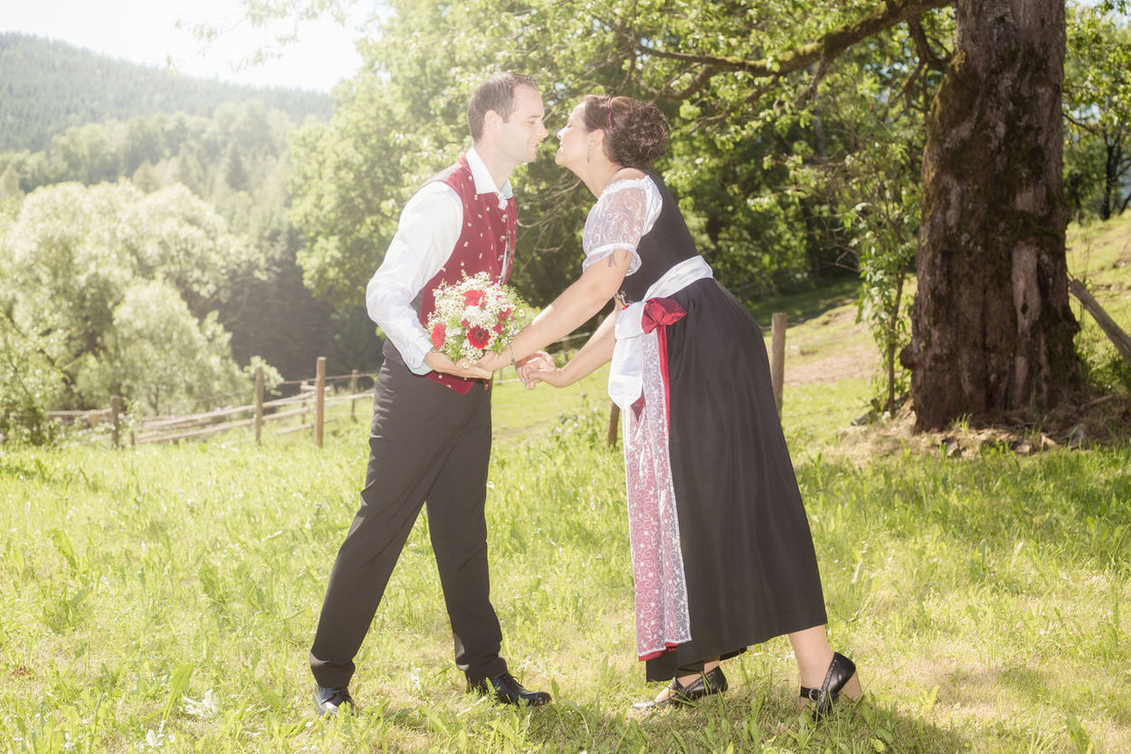 Lovely couple with traditional bavarian tracht Bonding Bride Bridegroom Celebration Cheerful Day Field Full Length Grass Happiness Life Events Love Men Nature Outdoors Standing Togetherness Tree Two People Wedding Wedding Dress Young Adult Young Couple Young Men Young Women