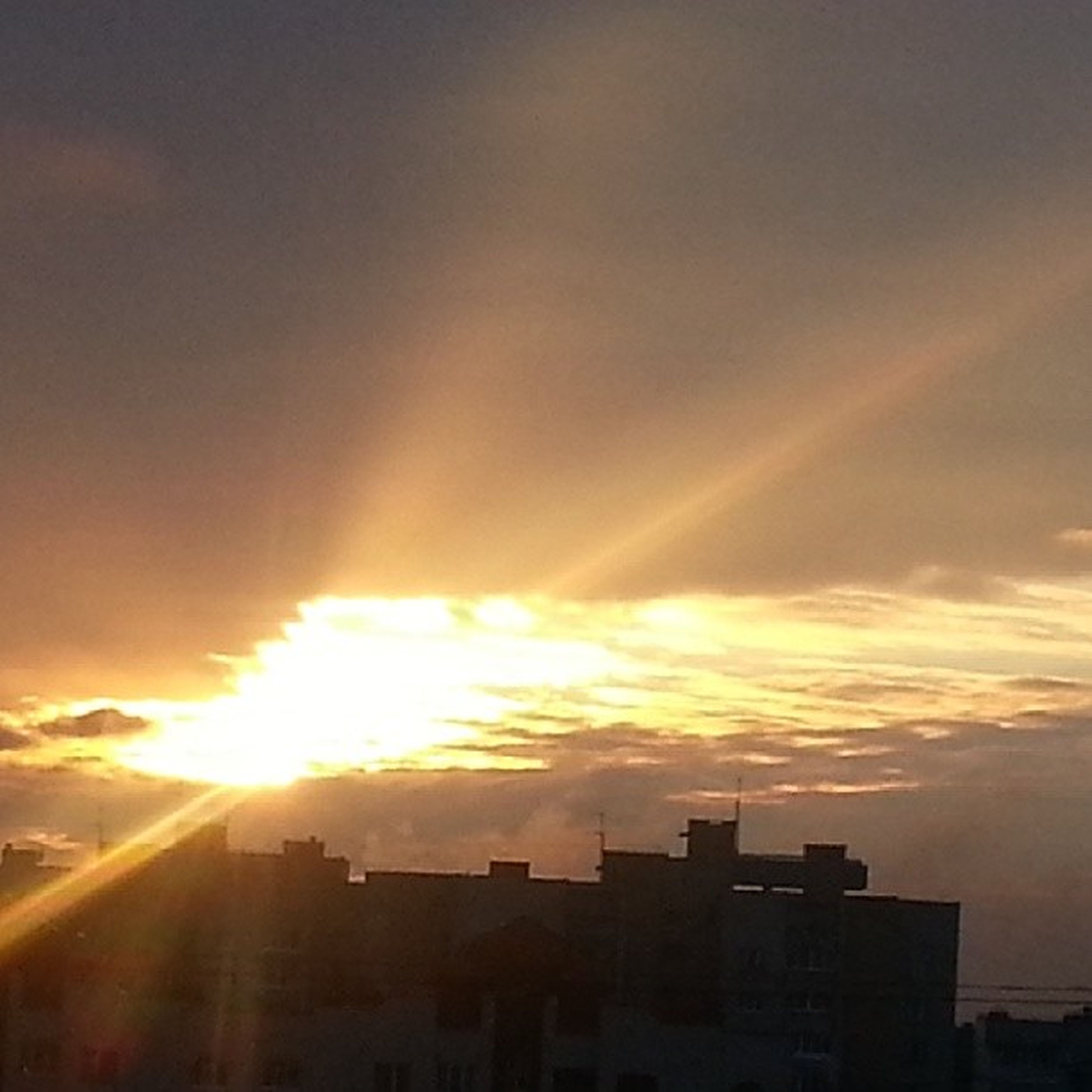 sunset, architecture, building exterior, sun, built structure, orange color, sky, sunbeam, sunlight, city, silhouette, lens flare, cloud - sky, building, outdoors, residential building, low angle view, residential structure, nature, no people