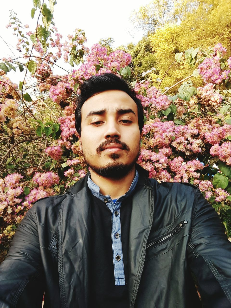 front view, real people, flower, one person, mid adult men, young adult, growth, nature, day, tree, jacket, outdoors, young men, looking at camera, leisure activity, lifestyles, plant, portrait, park - man made space, standing, beauty in nature, fragility, close-up