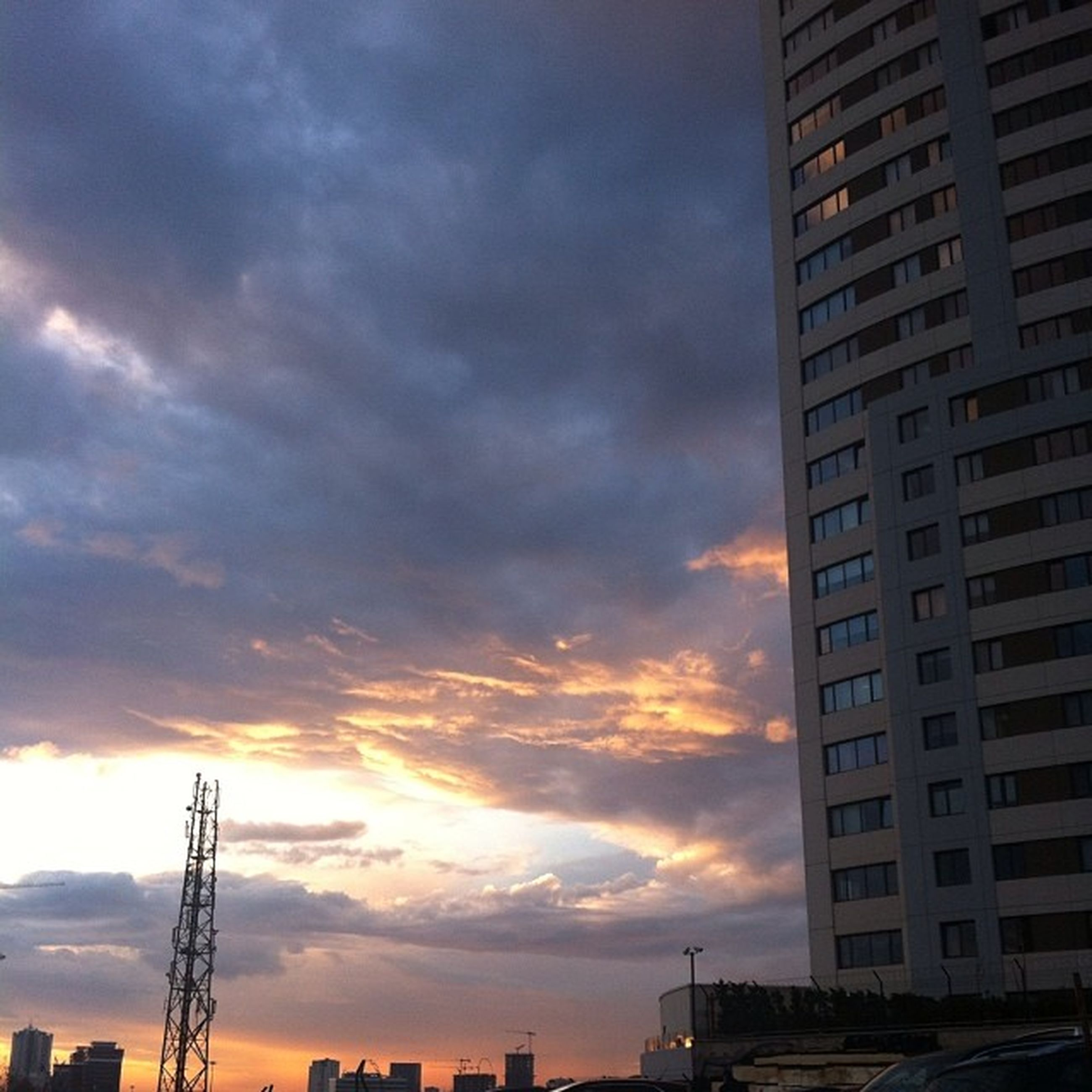 building exterior, architecture, built structure, sky, sunset, cloud - sky, city, low angle view, cloudy, silhouette, building, cloud, residential building, weather, residential structure, orange color, overcast, dramatic sky, dusk, outdoors