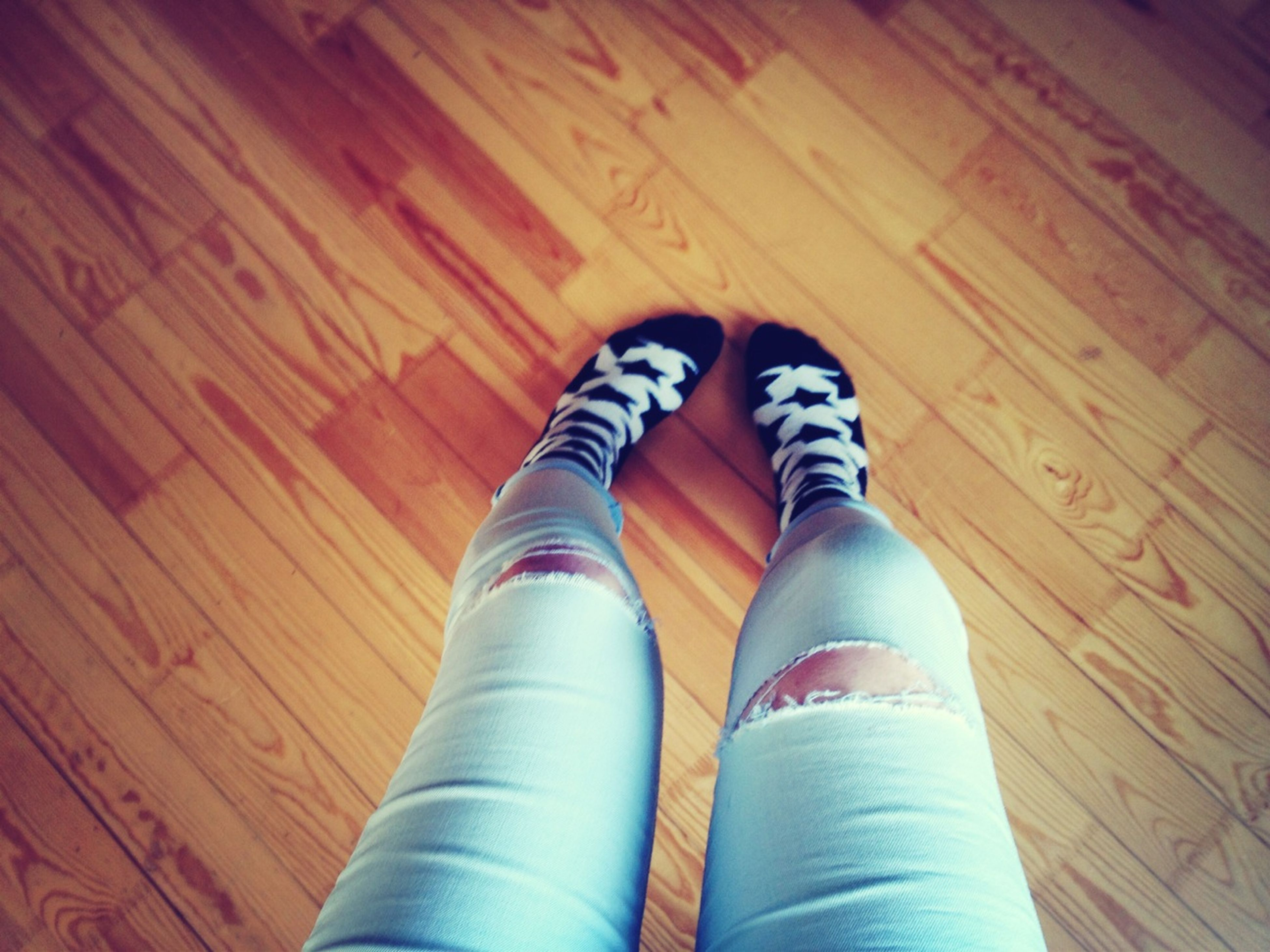 low section, shoe, indoors, person, wood - material, high angle view, personal perspective, hardwood floor, wooden, one person, footwear, flooring, human foot, floor, directly above, close-up, brown, part of, jeans