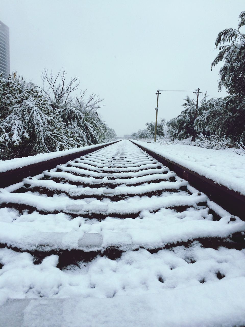 Scenic View Of Snow Covered Railroad Tracks