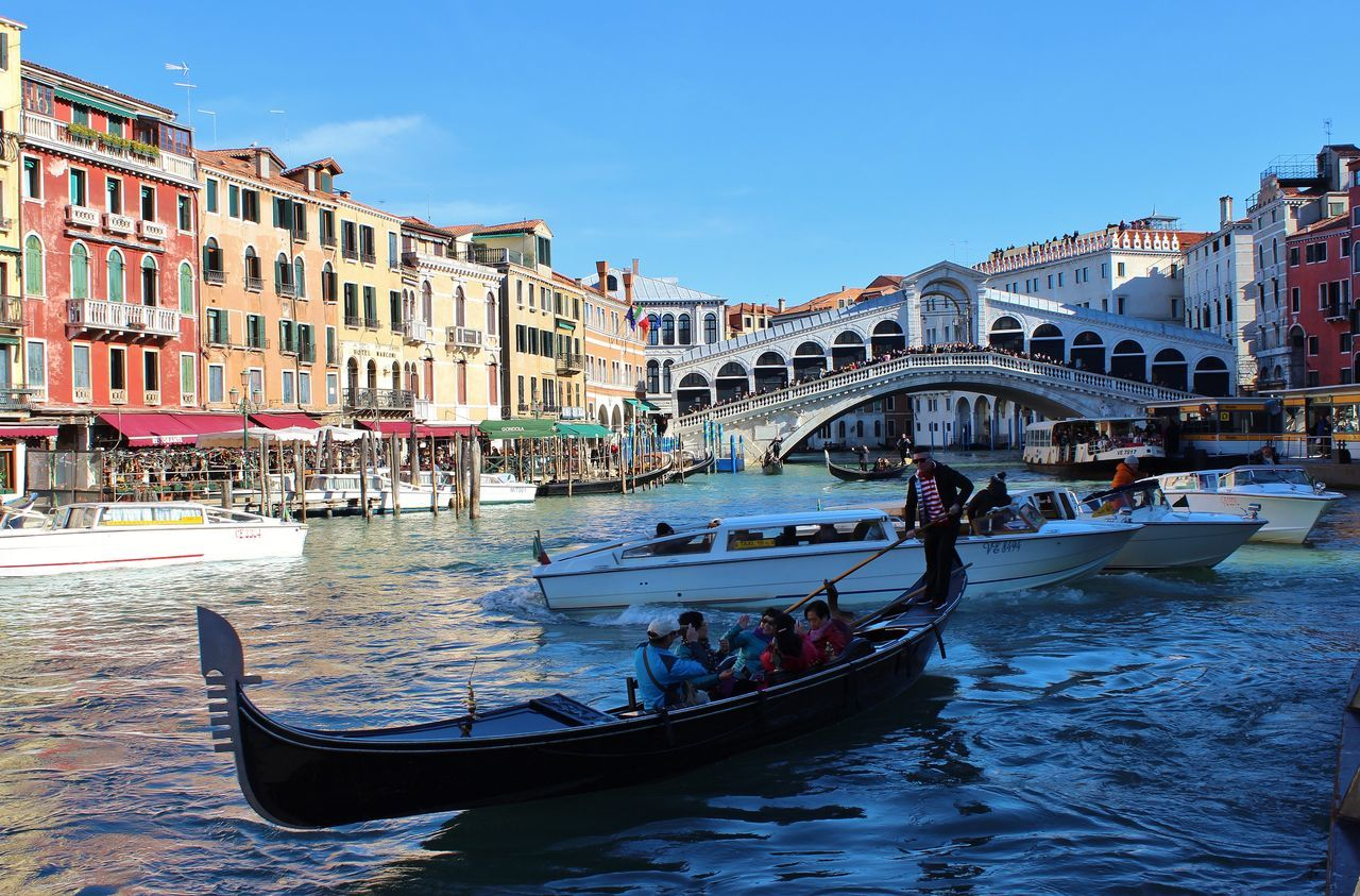 architecture, building exterior, built structure, real people, large group of people, transportation, nautical vessel, canal, men, water, sky, gondola, day, travel destinations, outdoors, gondola - traditional boat, mode of transport, women, leisure activity, vacations, nature, people