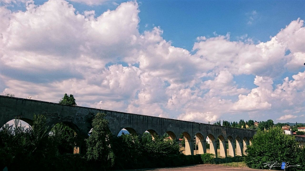 bridge - man made structure, connection, architecture, arch, sky, viaduct, built structure, cloud - sky, low angle view, outdoors, day, bridge, transportation, tree, no people, nature