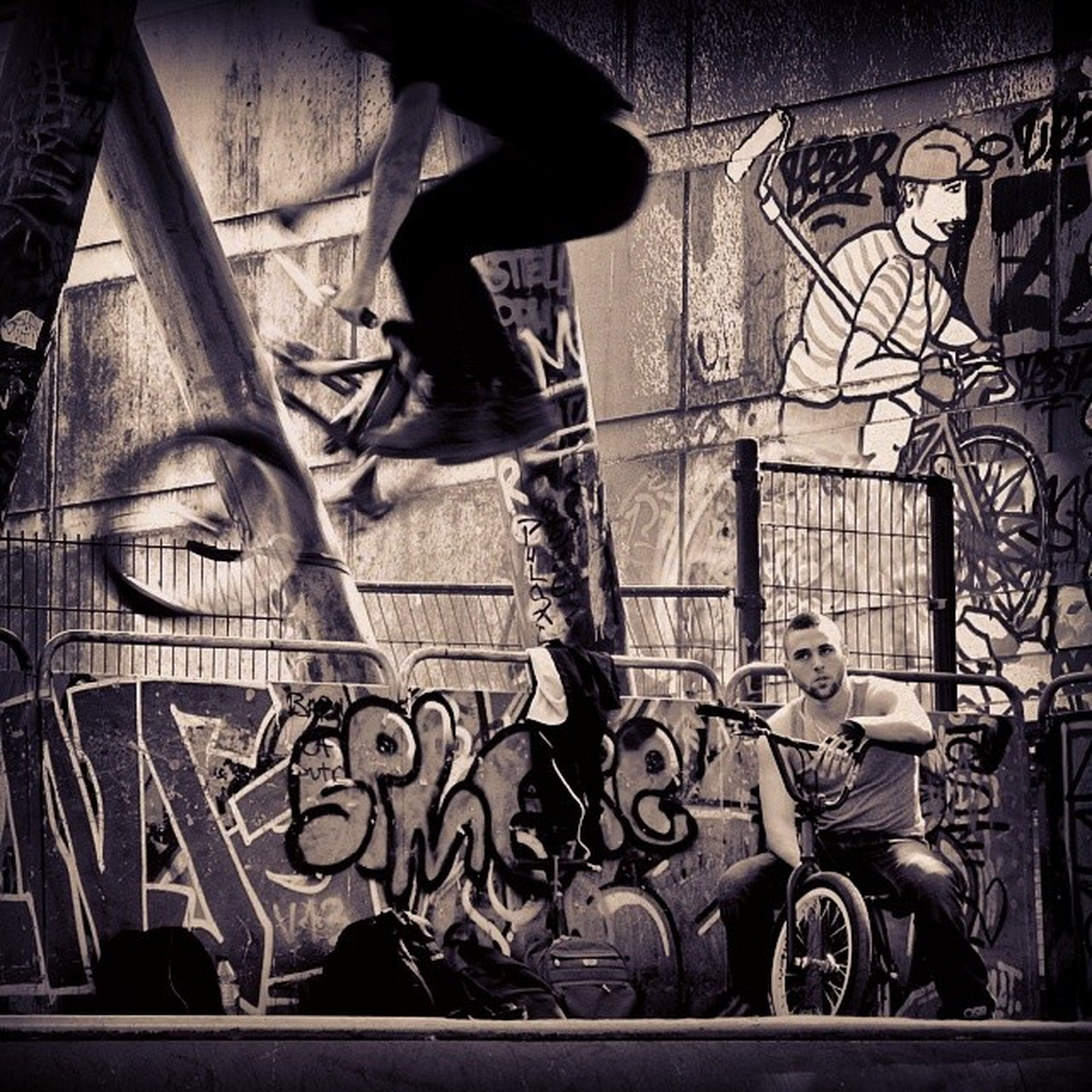 bicycle, men, built structure, architecture, building exterior, lifestyles, graffiti, leisure activity, full length, wall - building feature, shadow, side view, street, sunlight, transportation, standing, land vehicle, day