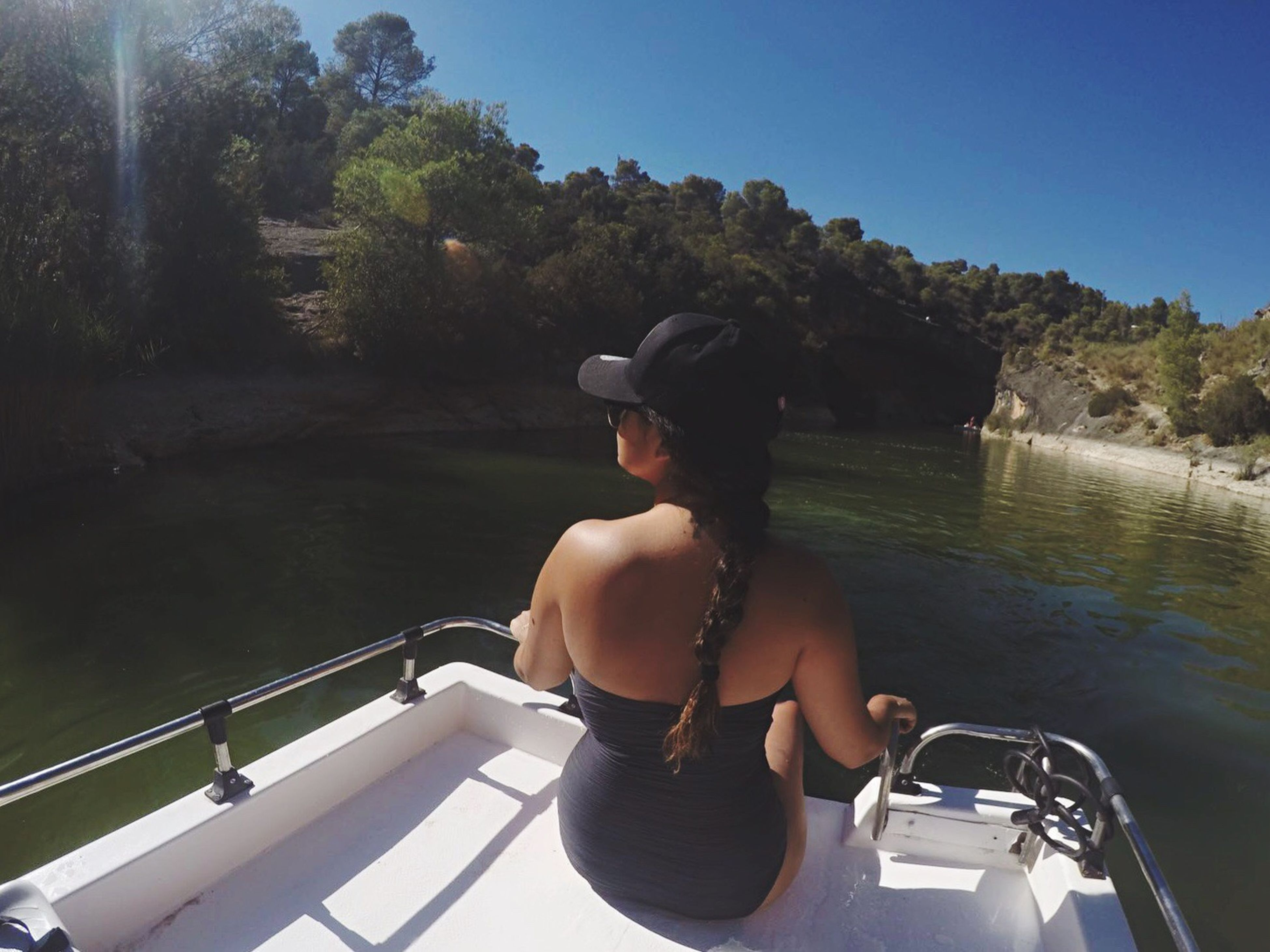nautical vessel, transportation, boat, water, mode of transport, tree, leisure activity, lifestyles, casual clothing, side view, sunlight, clear sky, vacations, travel, full length, young adult, river, person, day, journey, summer, nature, weekend activities