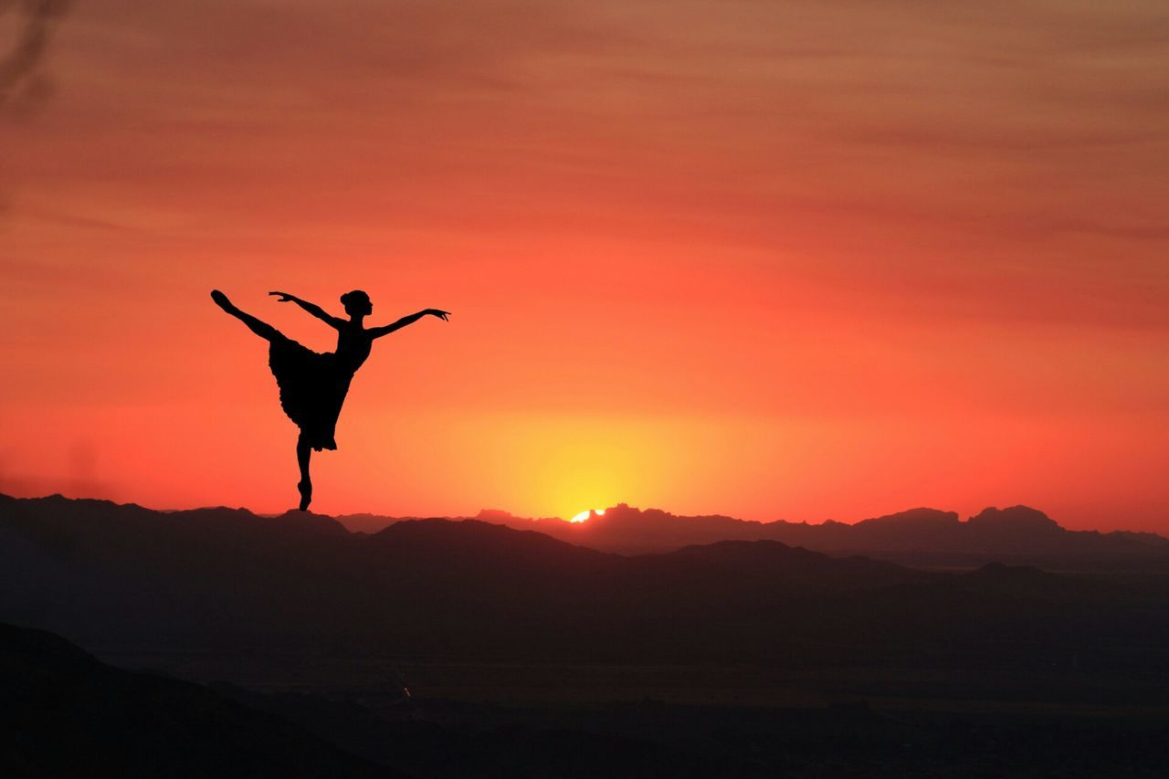 sunset, silhouette, orange color, nature, beauty in nature, real people, scenics, outdoors, leisure activity, one person, mountain, lifestyles, skill, full length, sky, handstand, energetic, day, people