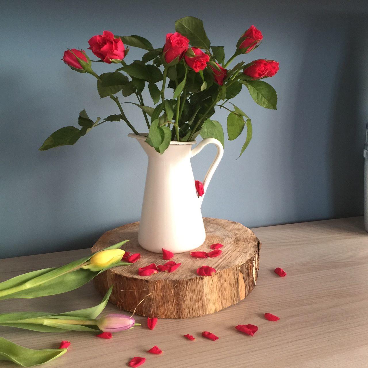 flower, indoors, vase, table, petal, freshness, home interior, decoration, fragility, red, wall - building feature, flower arrangement, flower head, rose - flower, leaf, potted plant, pink color, plant, flower pot, still life