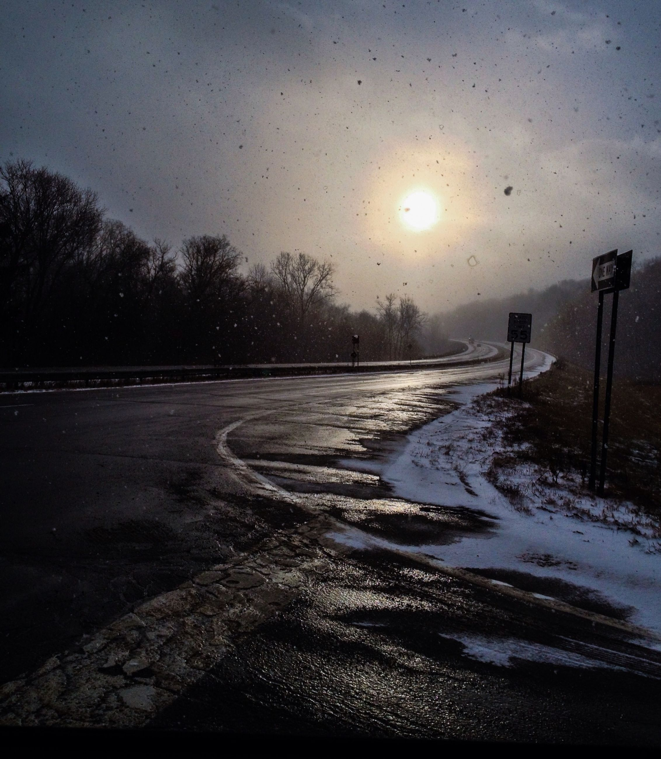 snow, cold temperature, winter, season, weather, street light, road, sky, sunset, tree, the way forward, wet, nature, tranquility, street, sun, transportation, beauty in nature, tranquil scene, frozen