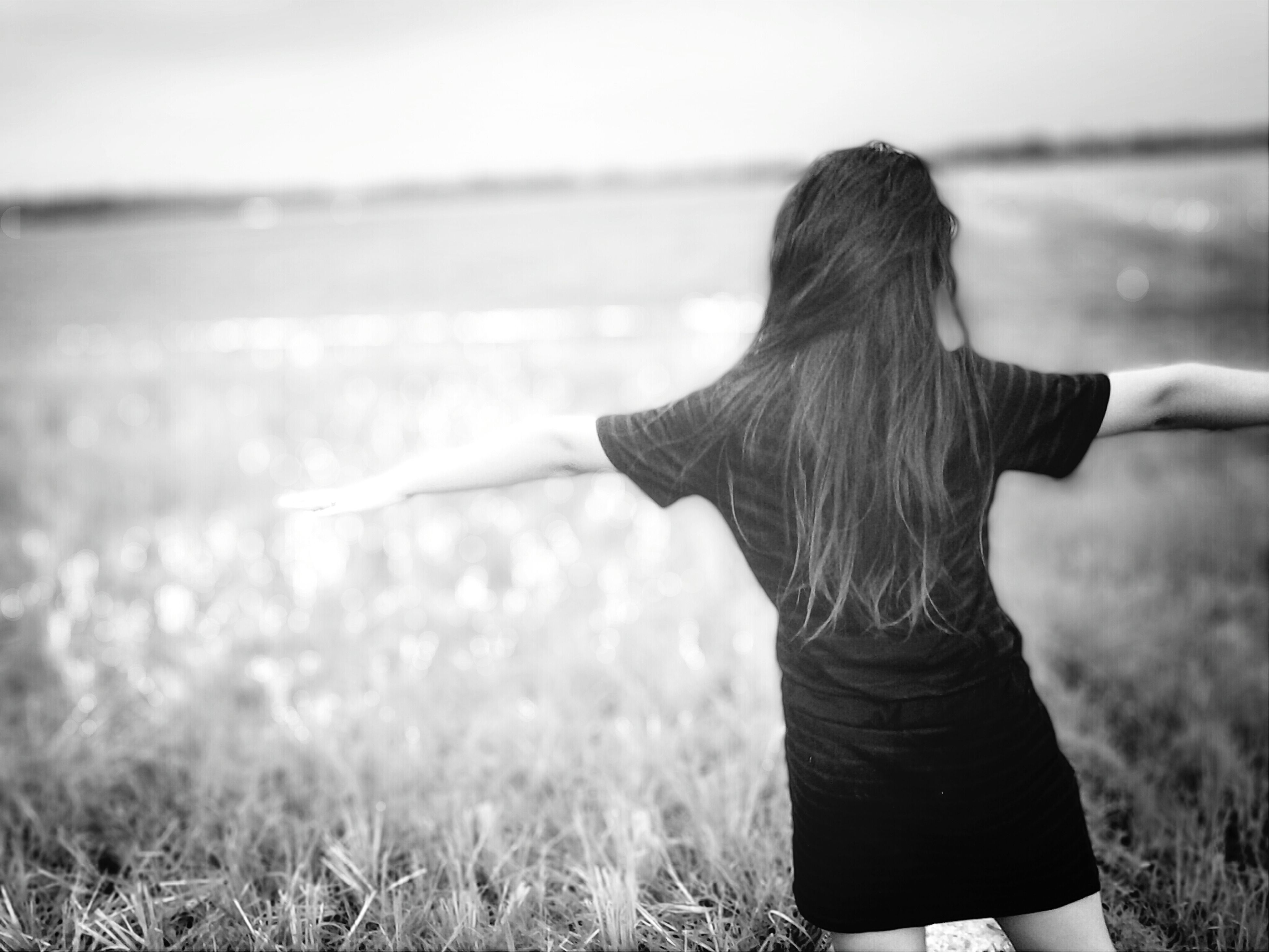 rear view, lifestyles, leisure activity, focus on foreground, water, grass, person, standing, tranquility, field, nature, tranquil scene, long hair, sky, lake, beauty in nature, outdoors, casual clothing