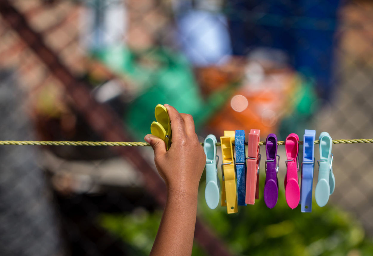 Close-up Multi Colored African Outdoors African American Afro Caribbean Garden Colorful Clothes Pegs Pegs Rope Colourful Focus On Foreground Human Hand Hanging String One Person Girl Child People Washing Line Clothes Peg Peg Person Of Colour Person Of Color