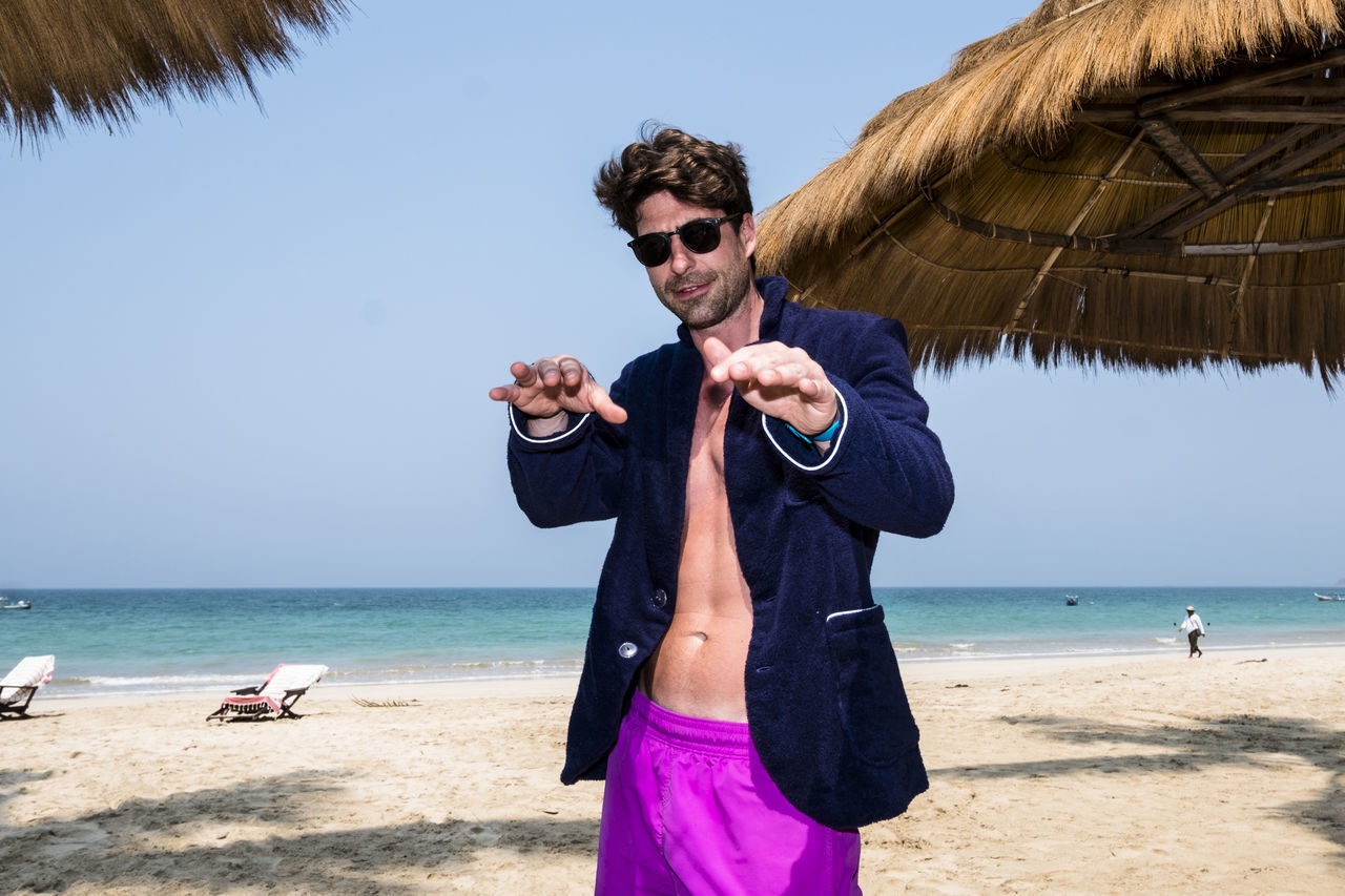 Stylish Man Gesturing While Standing At Beach
