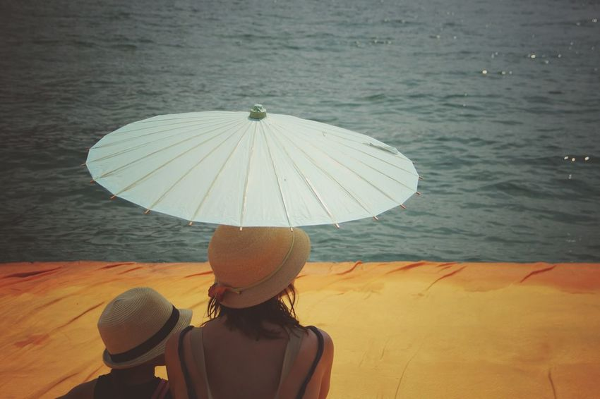 Walking on the Floating piers   Golden Moments  Mother Umbrella The Essence Of Summer Getting Inspired Point Of View Still Life People Fine Art Close-up The Innovator The Mix Up Edge Of Imagination The Floating Piers Sunshine Christo And The Floating Piers Tailored To You Original Experiences Feel The Journey Relaxing Showcase July 43 Golden Moments Lago D'Iseo EyeEm Italy  