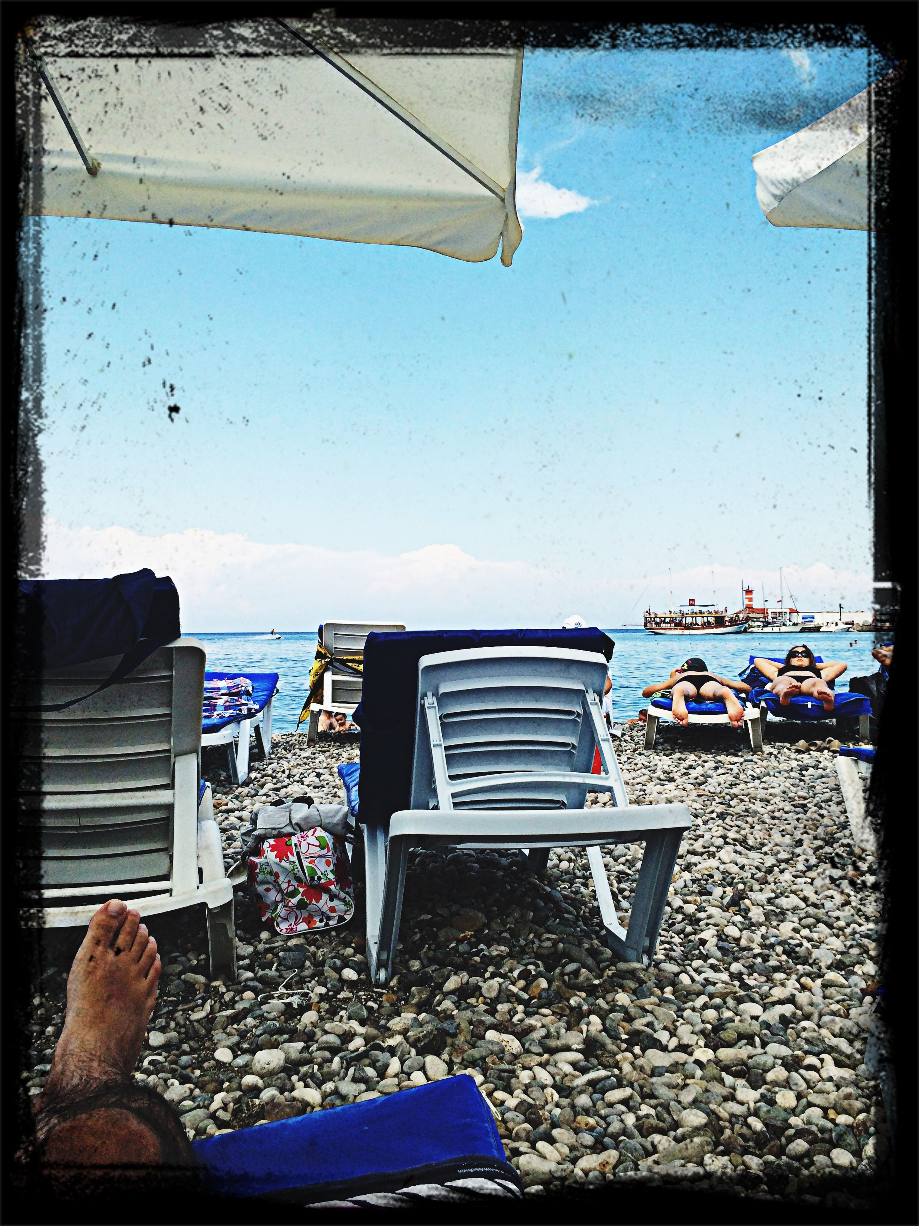 sea, beach, transfer print, lifestyles, leisure activity, men, auto post production filter, relaxation, person, sitting, water, sky, horizon over water, chair, vacations, beach umbrella, clear sky, shore