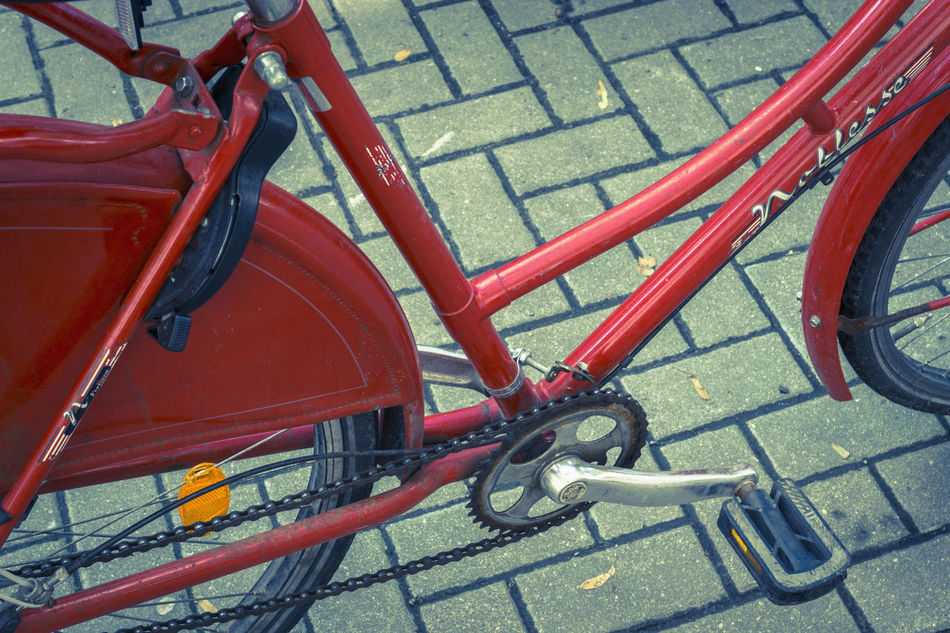 Close-up of red lady's bicycle Close Up Close-up Cropped Day Lady's Bicycle Land Vehicle Mode Of Transport No People Outdoors Parked Parking Parking Lot Part Of Red Stationary Tiled Street Tire Transportation Wheel
