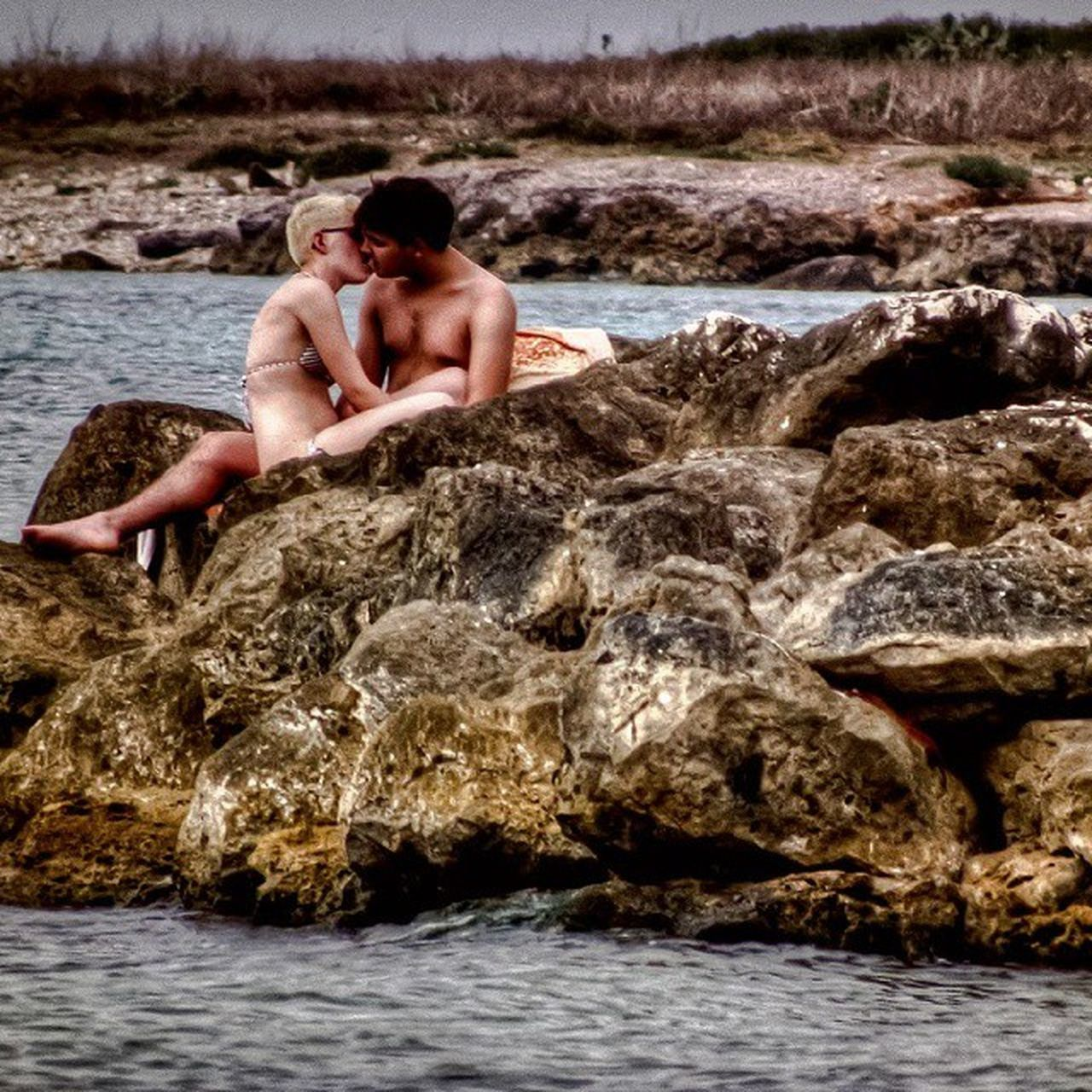 two people, rock - object, shirtless, togetherness, sea, water, leisure activity, adventure, sitting, day, real people, vacations, men, outdoors, nature, full length, people, adult, young adult, adults only