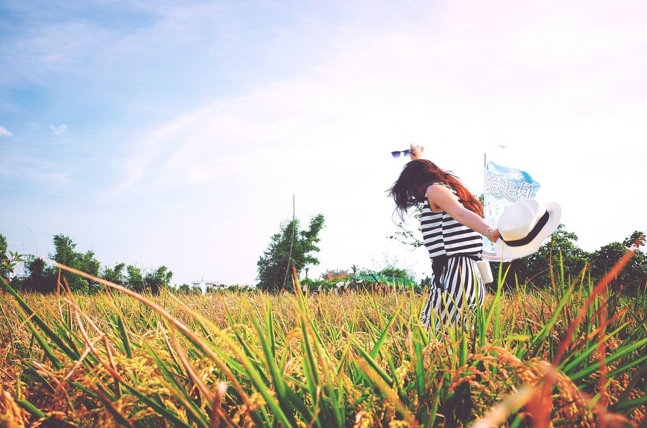 Side View Of Cheerful Woman Holding Hat On Grassy Field Against Sky