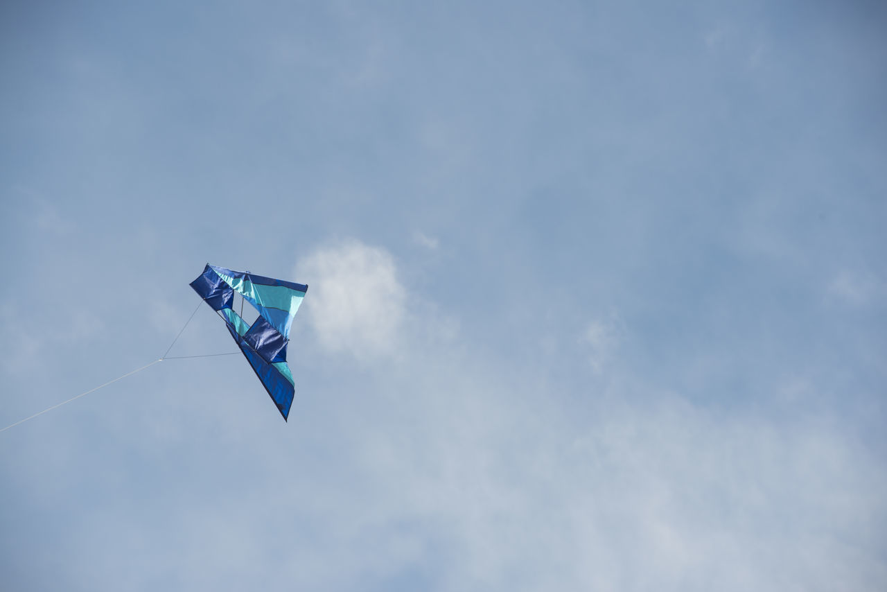 Low Angle View Of Kite In Cloudy Sky