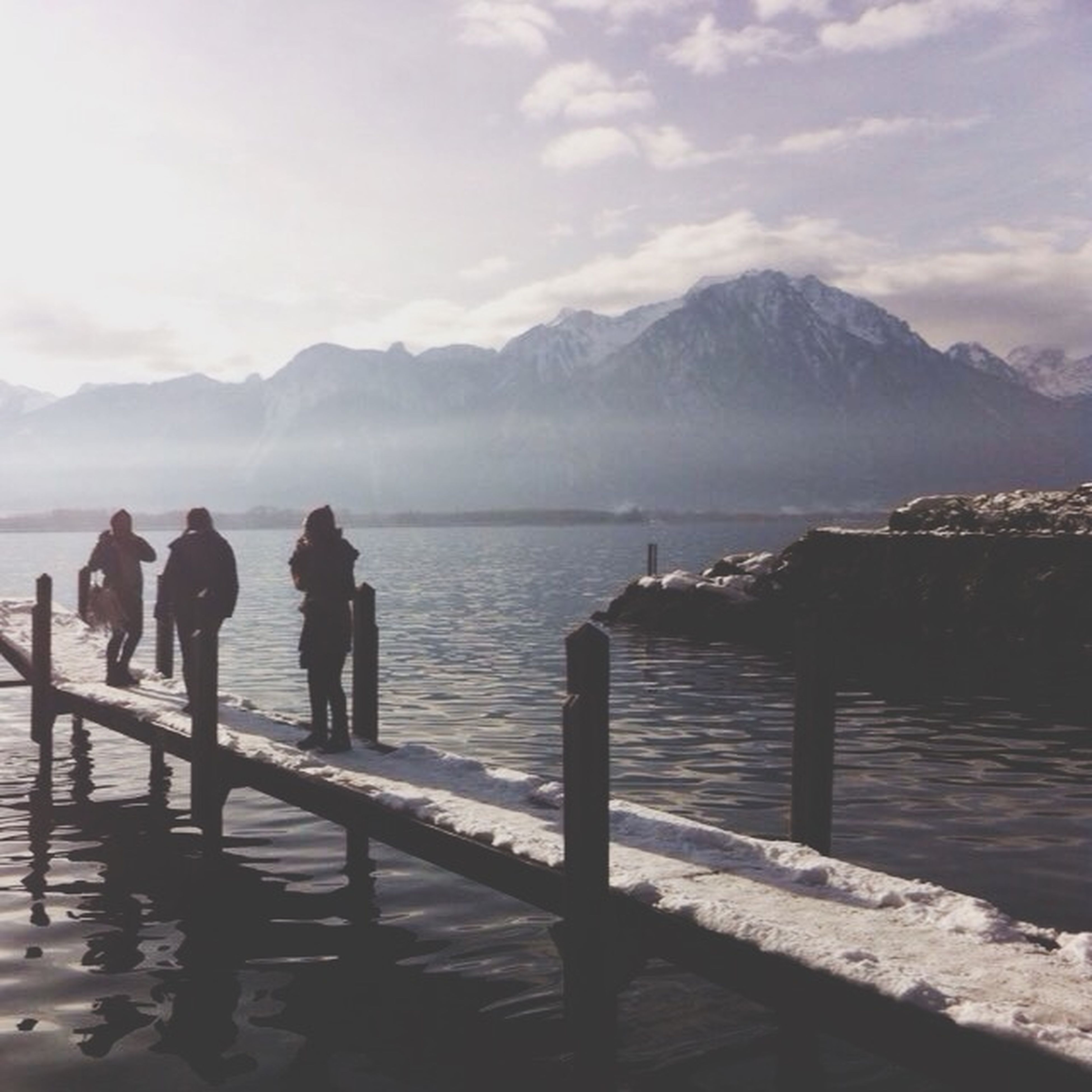 water, mountain, sky, sea, railing, men, lifestyles, mountain range, scenics, nature, tranquility, leisure activity, tranquil scene, beauty in nature, person, cloud - sky, pier, standing, walking