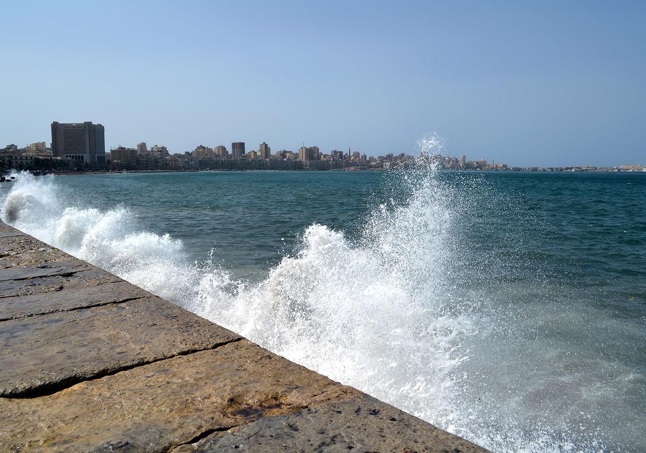 Sea Waves Splashing On Retaining Wall Against Clear Sky