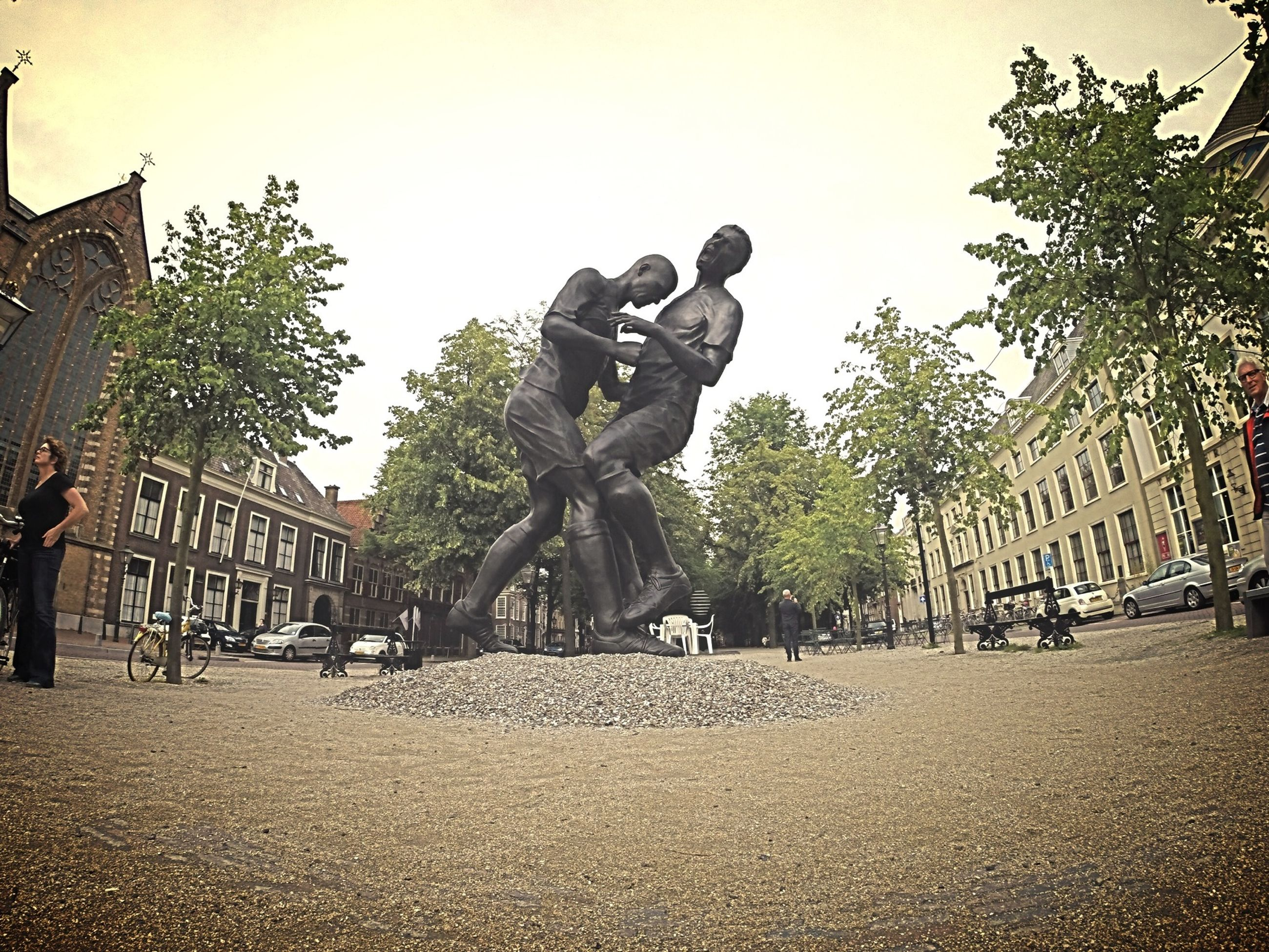 architecture, building exterior, built structure, tree, city, men, art and craft, statue, sculpture, clear sky, art, street, lifestyles, human representation, leisure activity, day, creativity, large group of people, city life