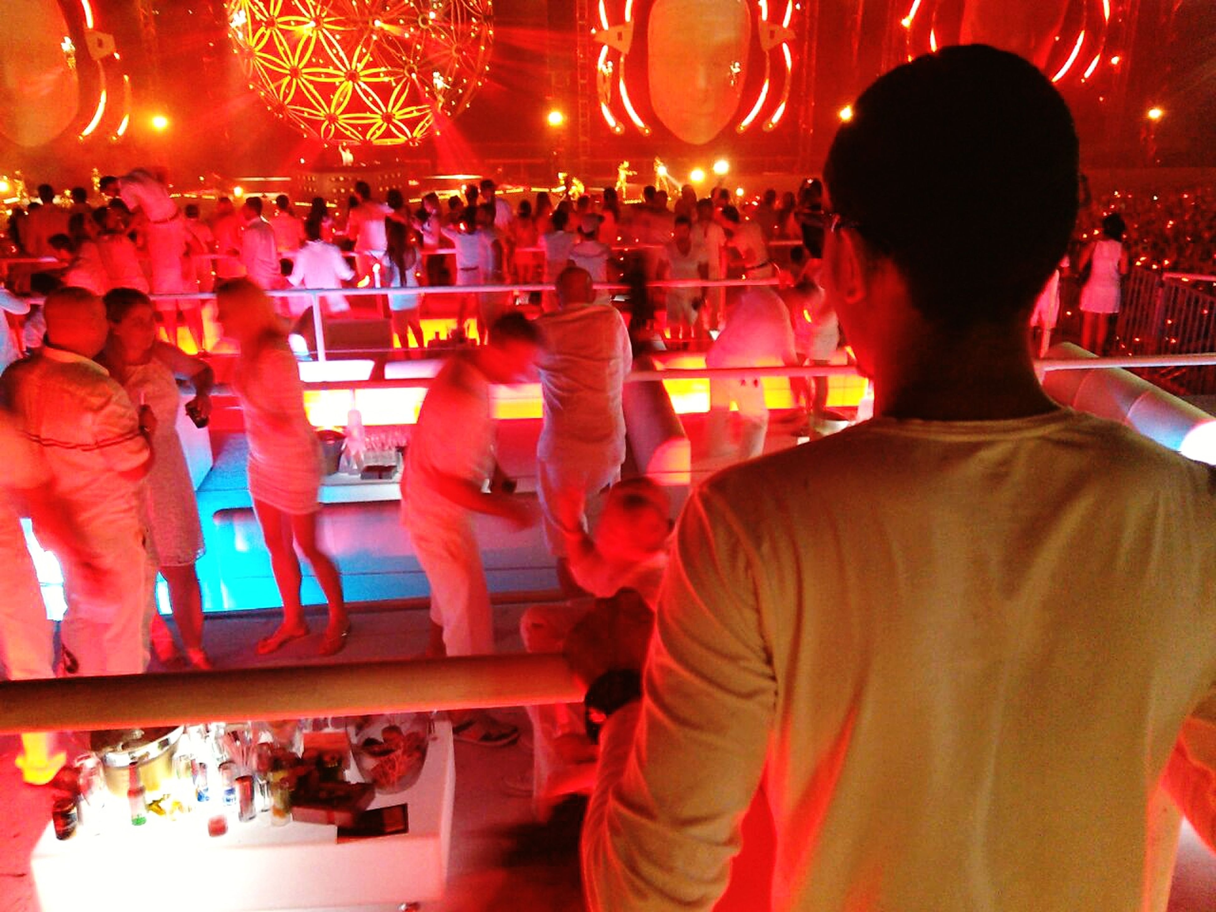 illuminated, large group of people, night, lifestyles, men, person, leisure activity, crowd, indoors, arts culture and entertainment, nightlife, lighting equipment, event, enjoyment, music, performance, stage - performance space, celebration