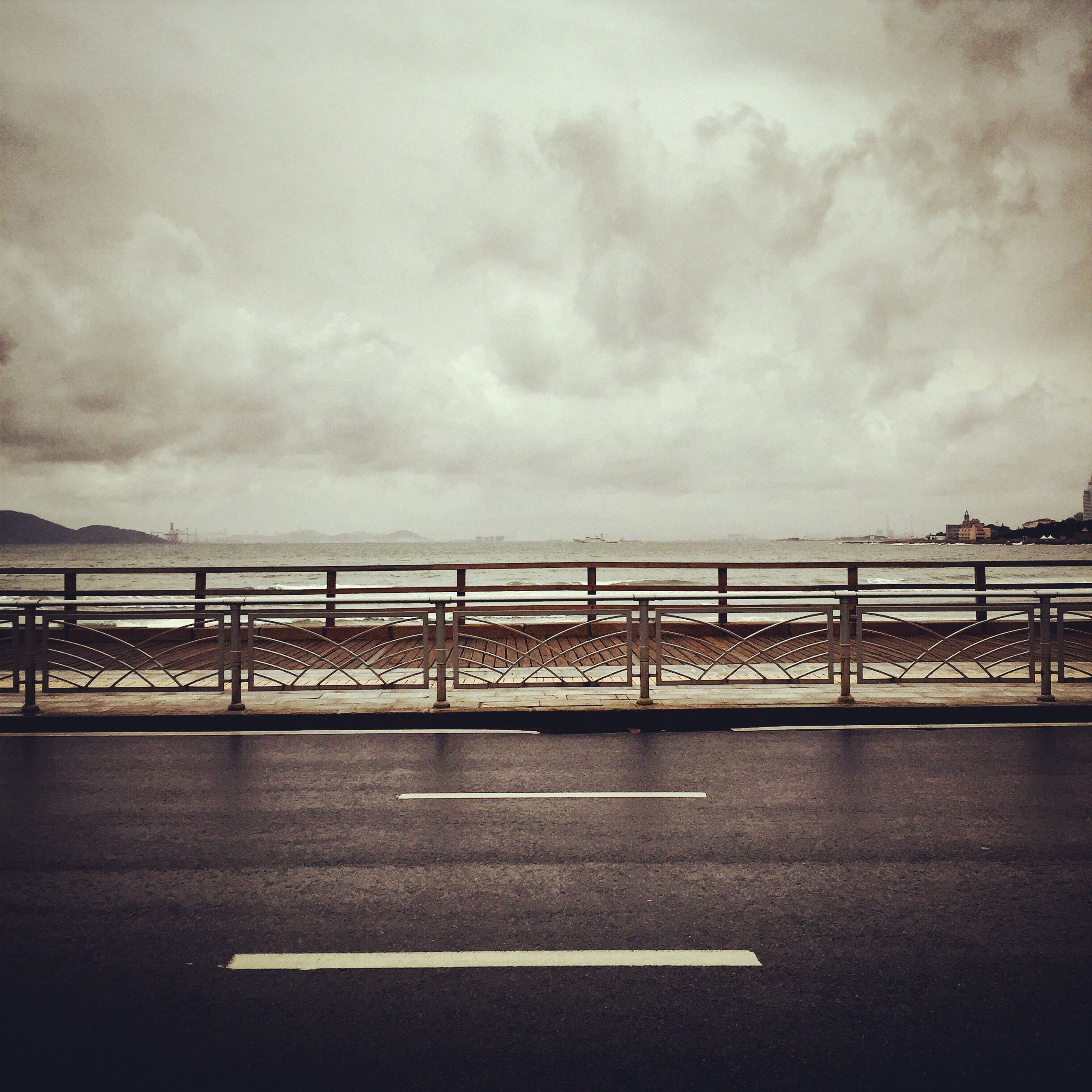 sky, bridge - man made structure, cloud - sky, connection, transportation, built structure, cloudy, railing, architecture, bridge, cloud, water, river, road, engineering, outdoors, overcast, no people, road marking, nature