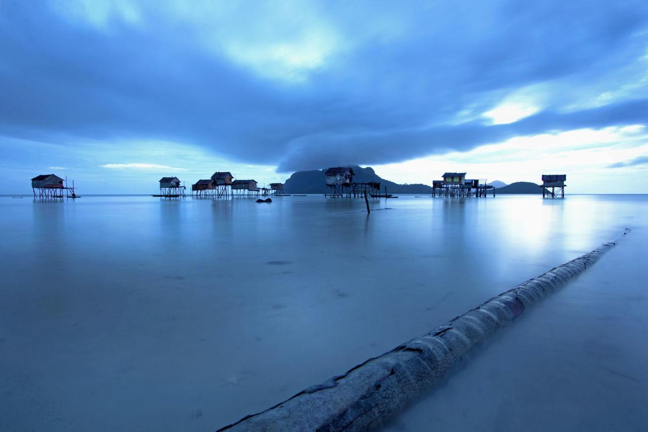 Stilt Houses In Lake Against Cloudy Sky